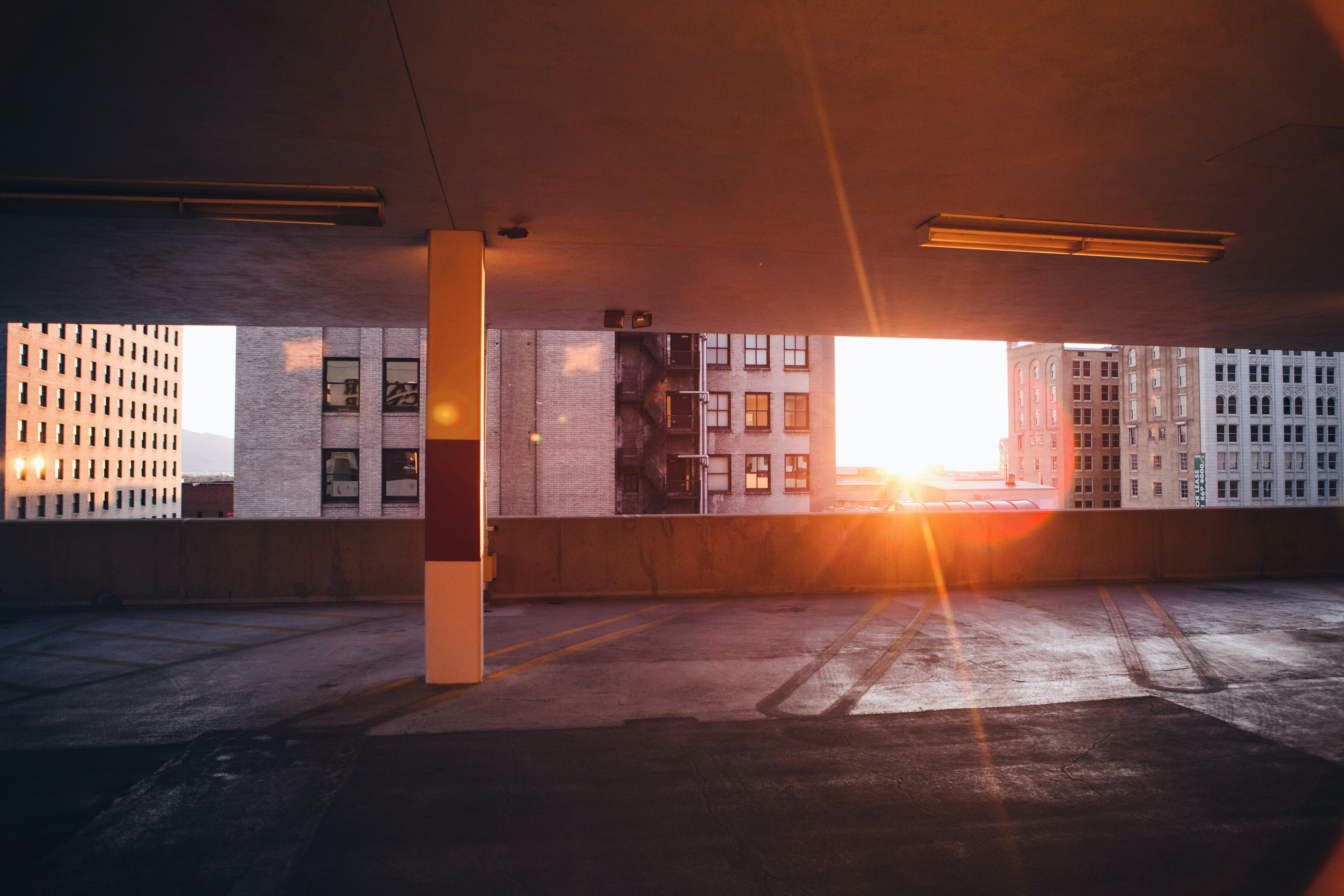 Sun peeking through an empty city car park next to buildings in Salt Lake City