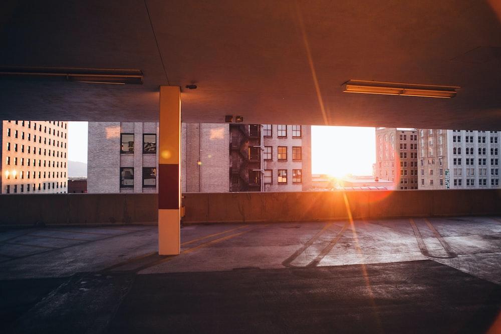 Sun peeking through an empty city car park next to buildings in Salt Lake City