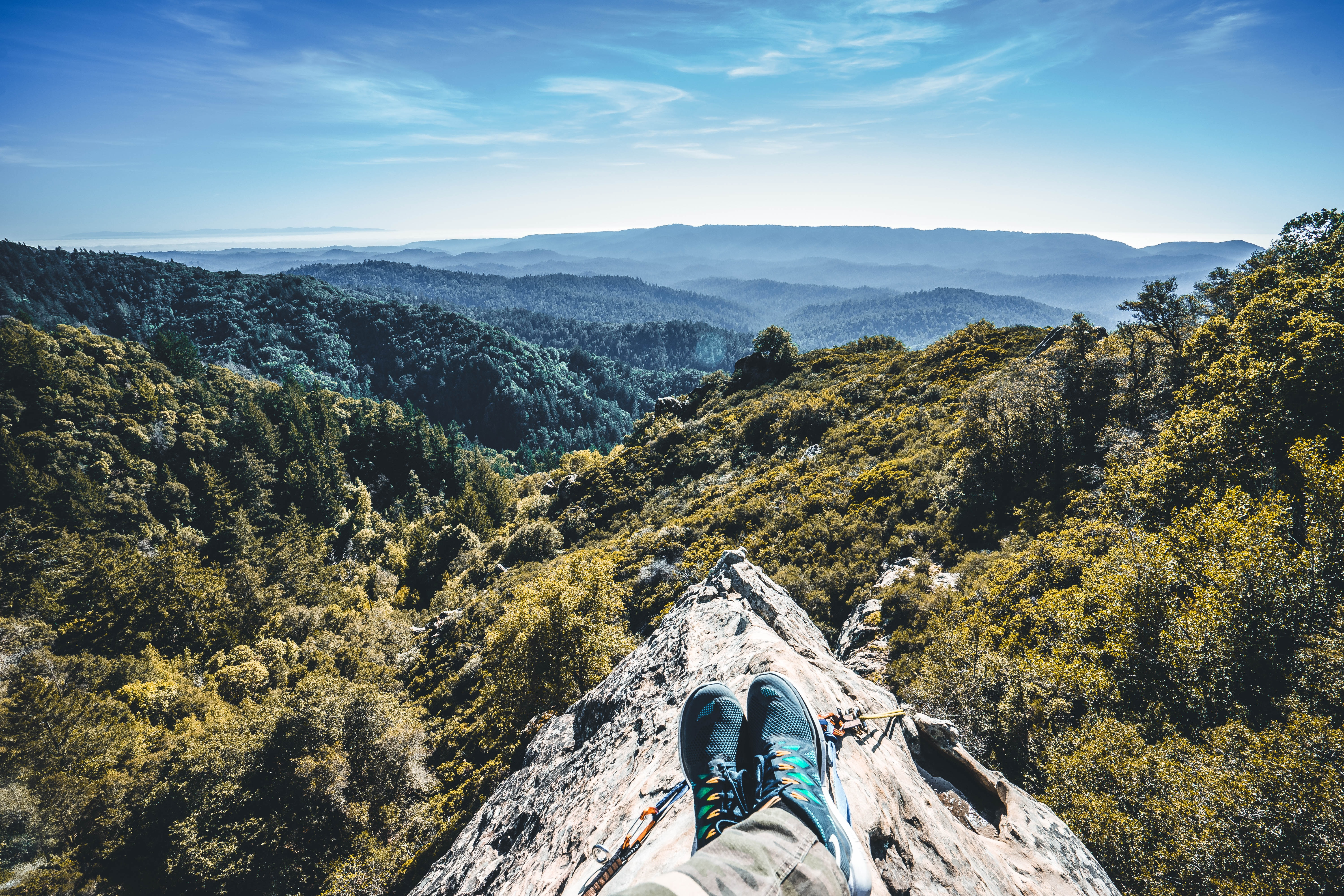 A mountaineer's outstretched legs on a rocky ridge
