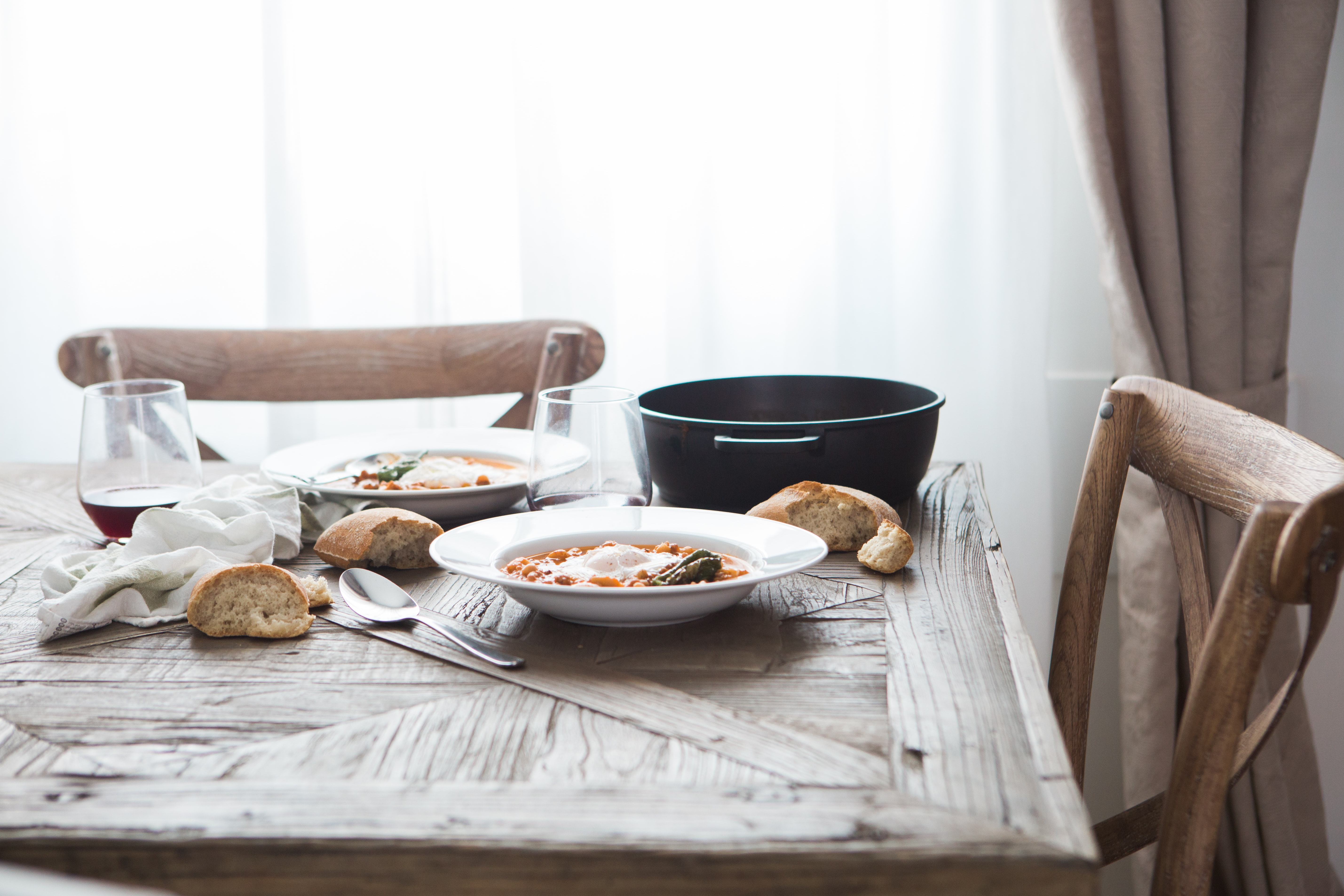Two deep dishes with a hearty meal, pieces of bread and wine glasses on a wooden table