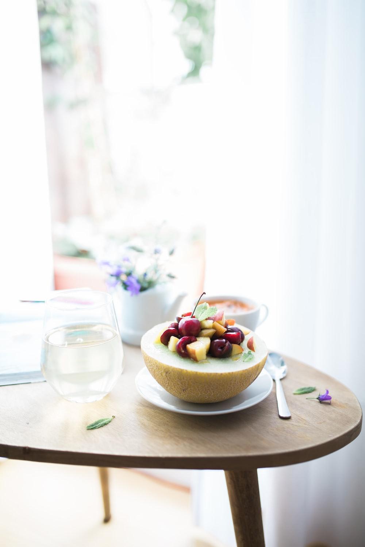 dessert dish filled white plate beside spoon