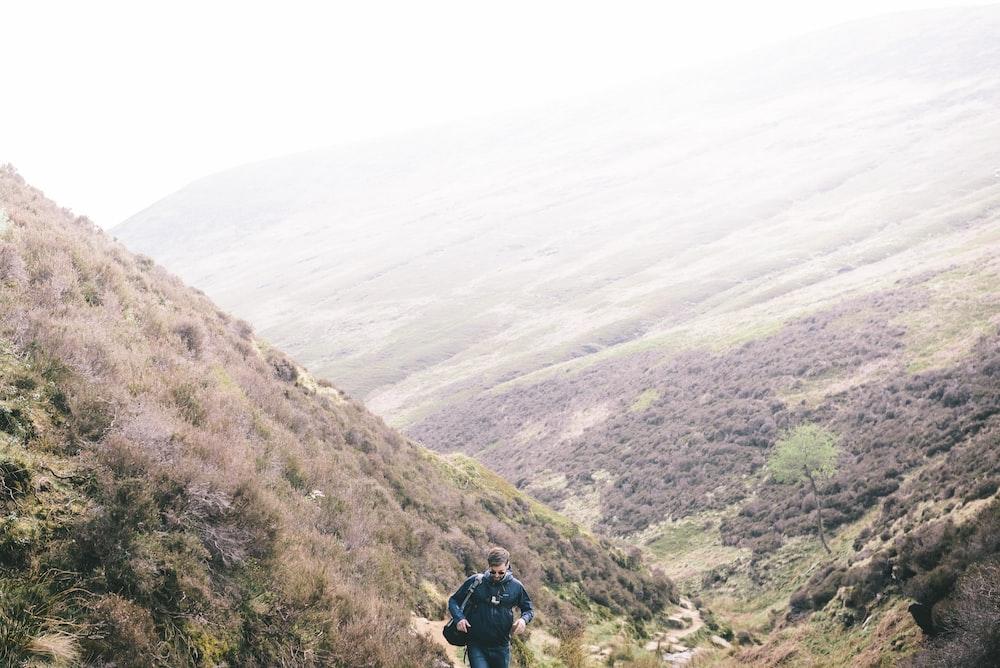 man walking on mountain during daytime