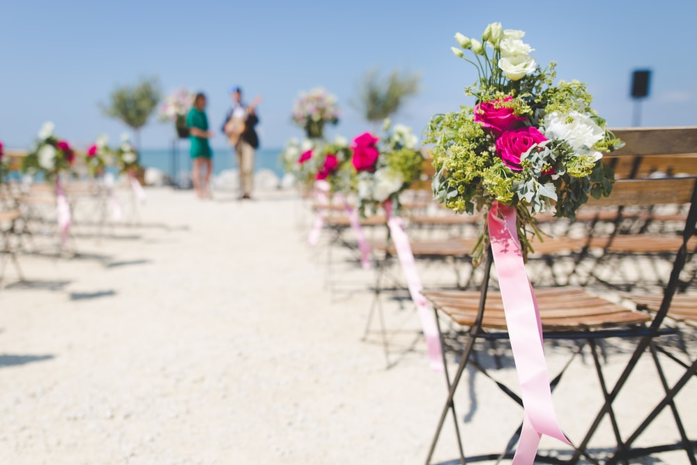 A beachfront wedding is being set up while a musician does a soundcheck