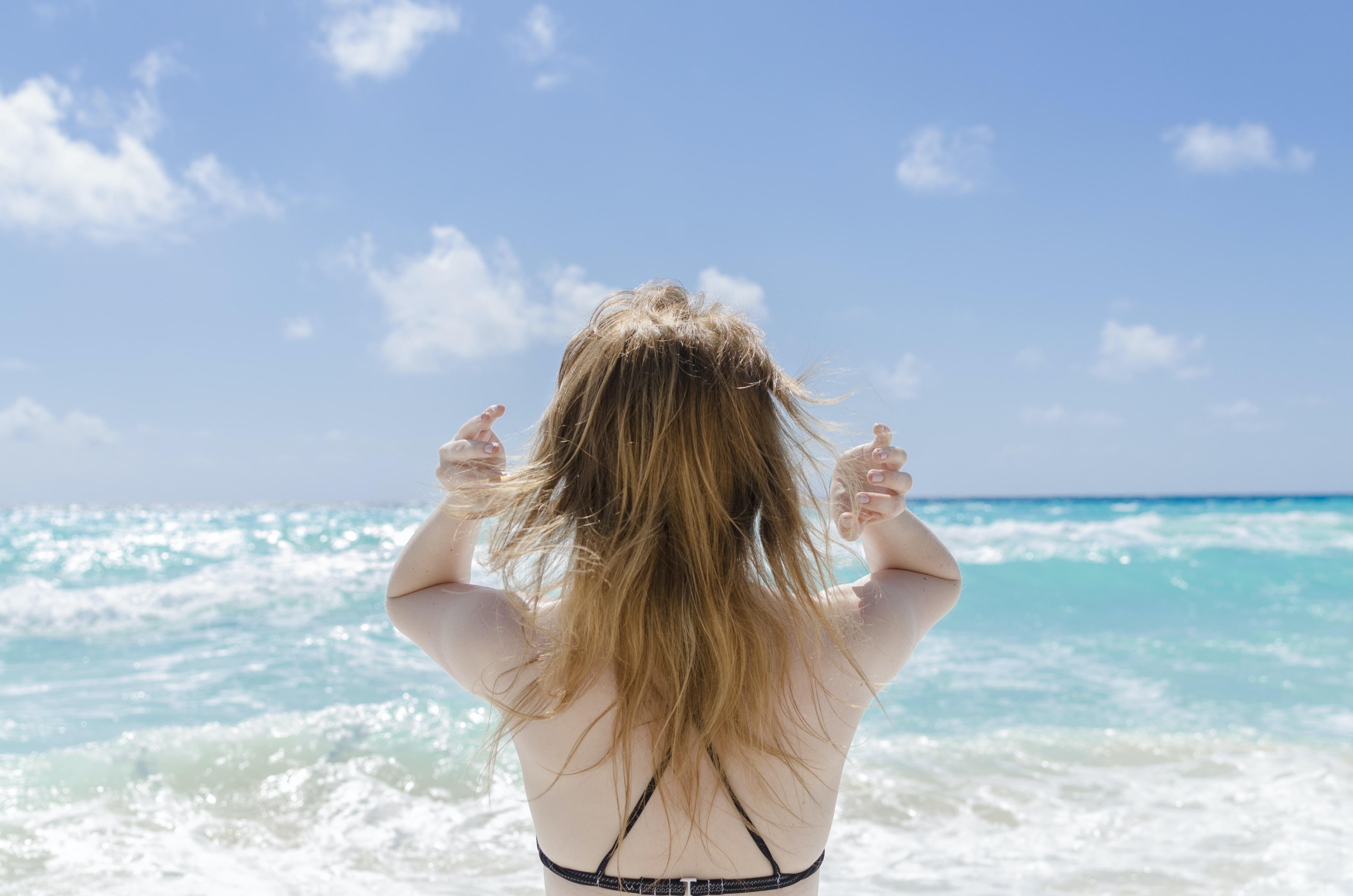 woman wearing black bra raising both arms facing towards the sea at daytime