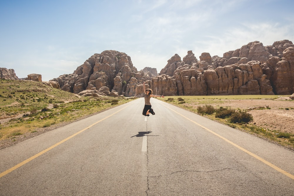woman jumping on the middle of road