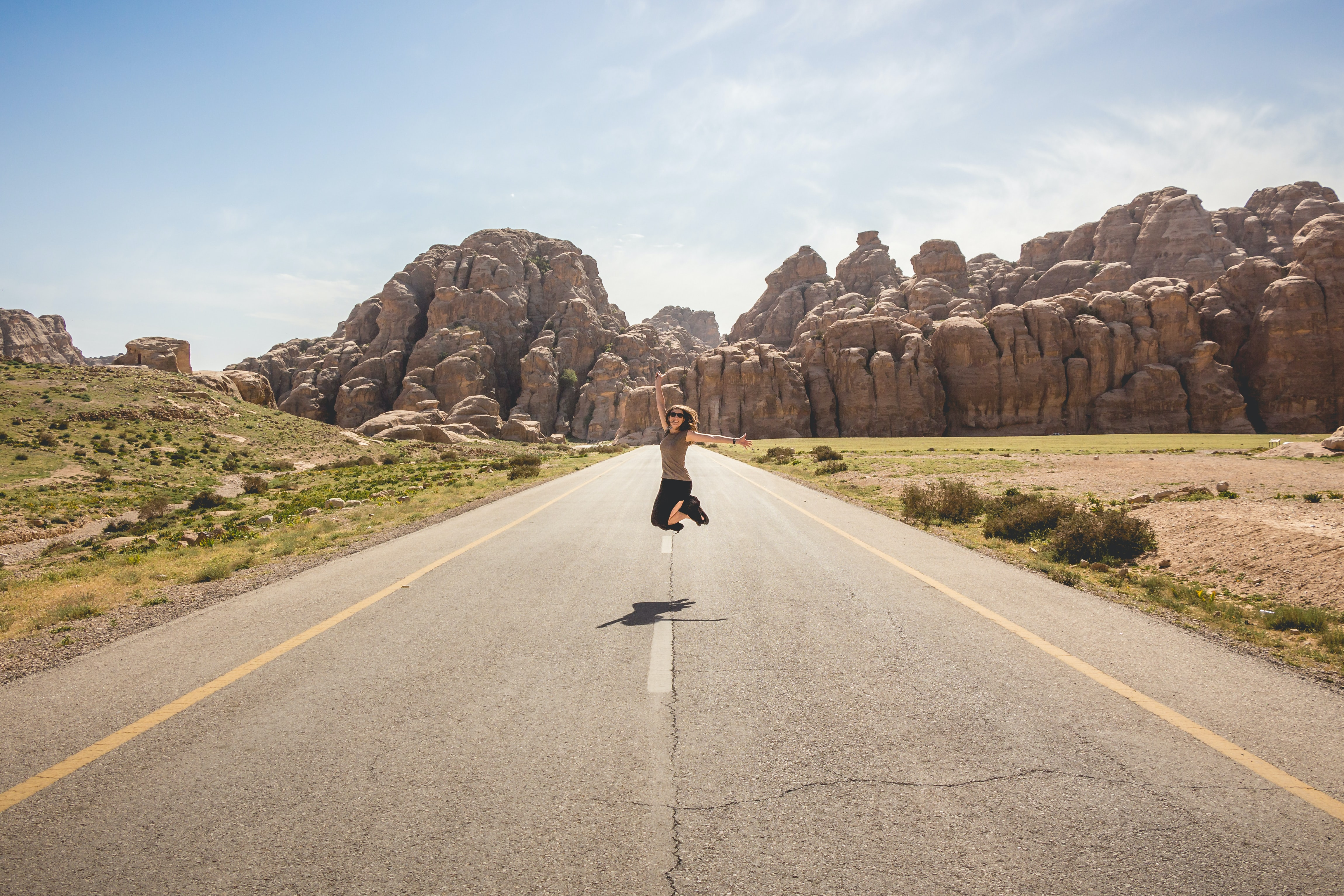 A woman in sunglasses jumps up in the middle of an empty road with rocky outcroppings in the background