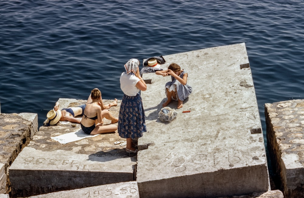 Women in swimsuits and vintage clothing sunbathing on cement cubes by the sea