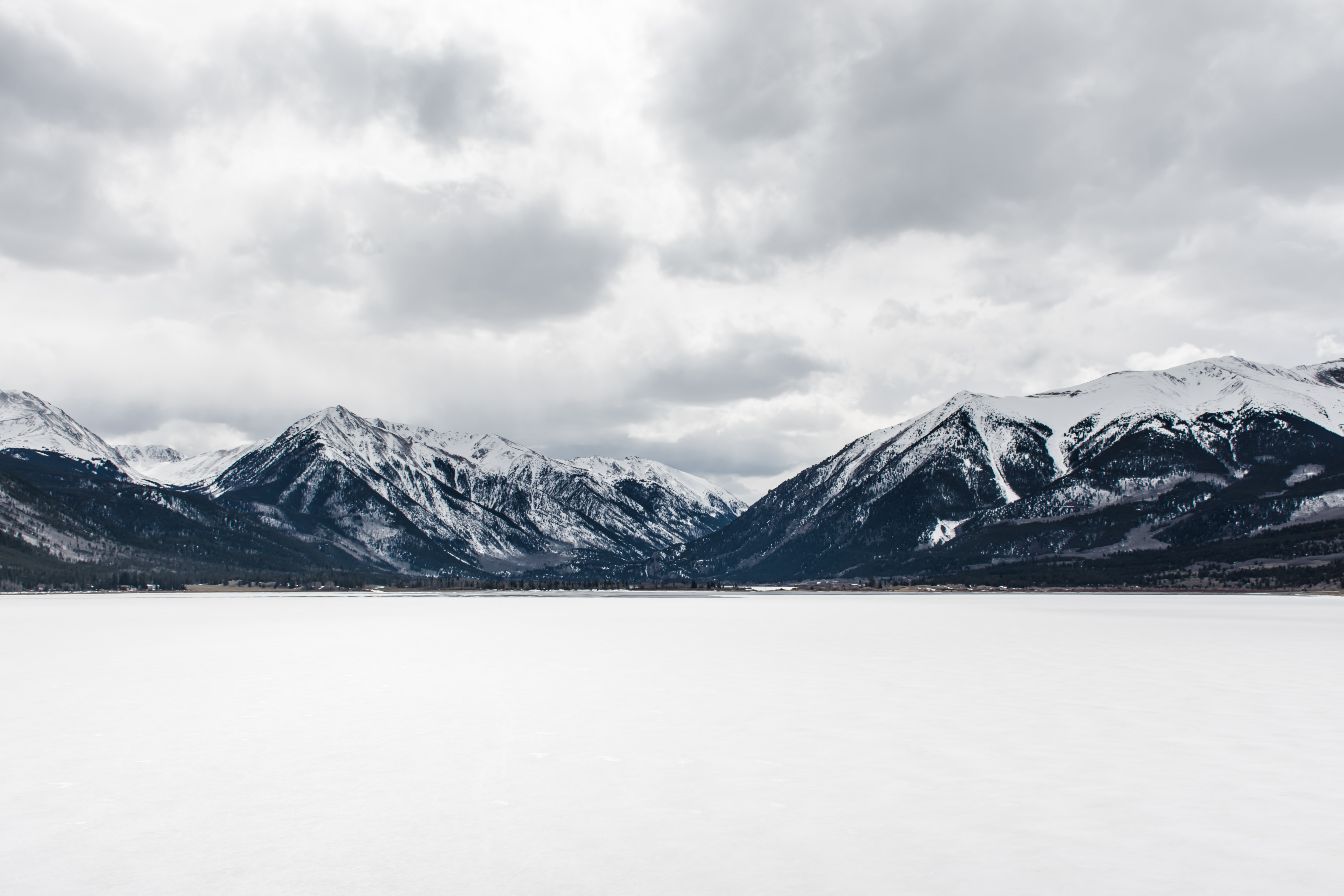 Cloudy overhead skies hovering over snowy mountain tops