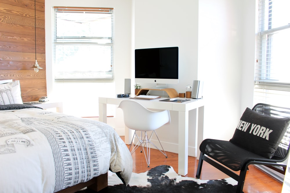 A bedroom with a large bed and a computer desk