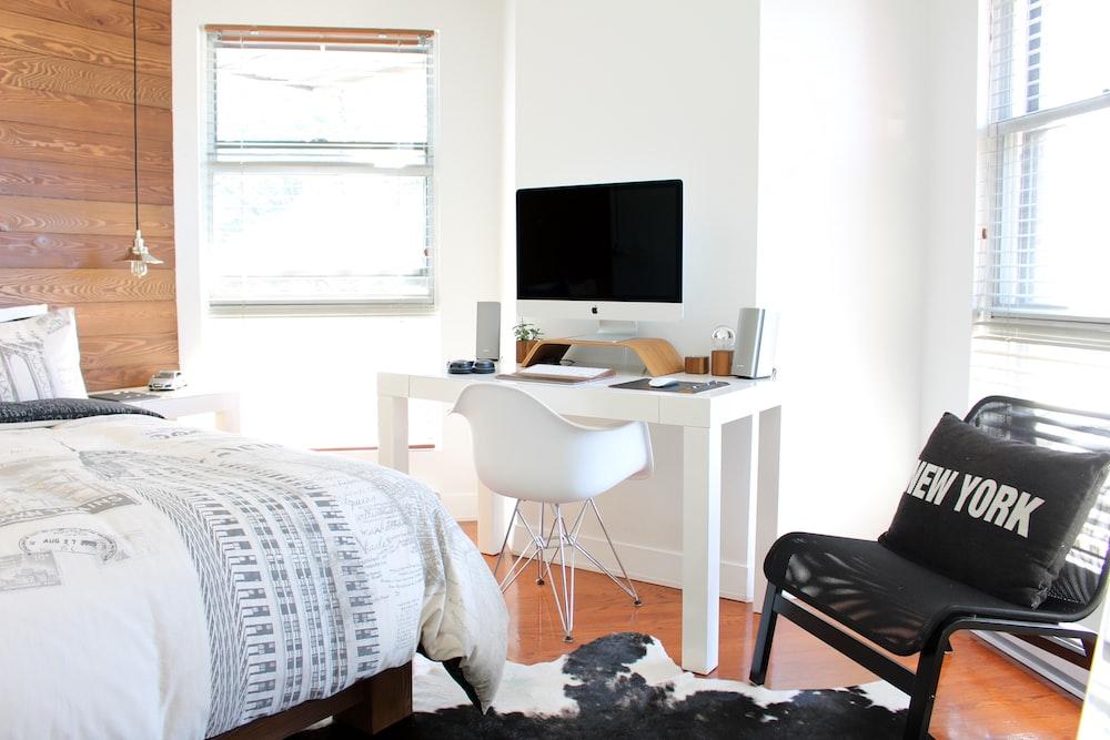 white wooden desk near bed inside the room