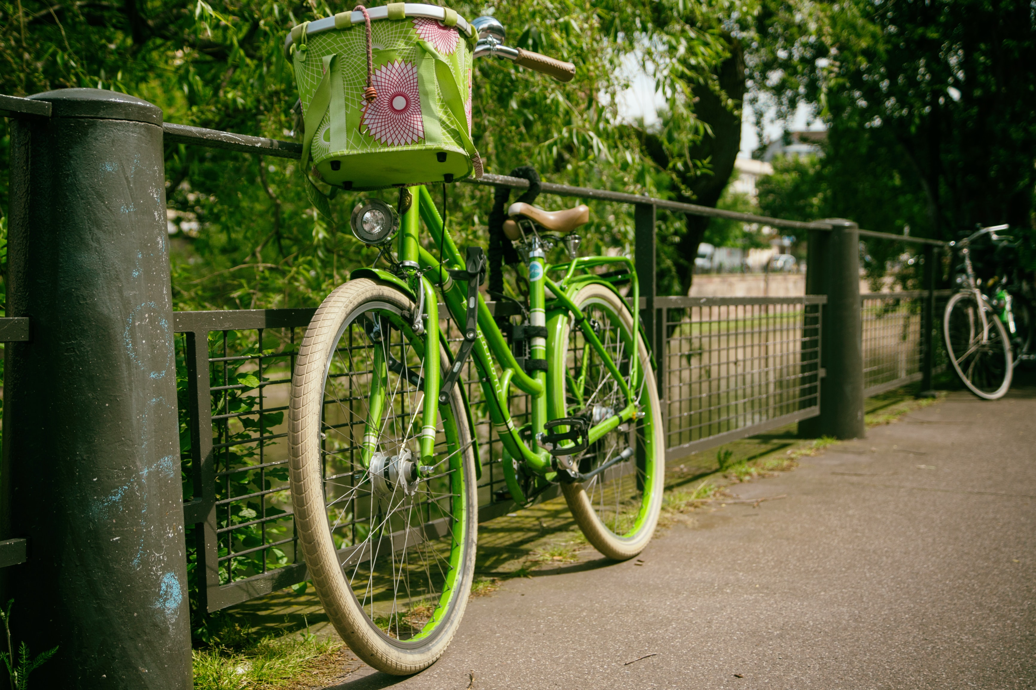 green cruiser bike with basket leaning on gray rail
