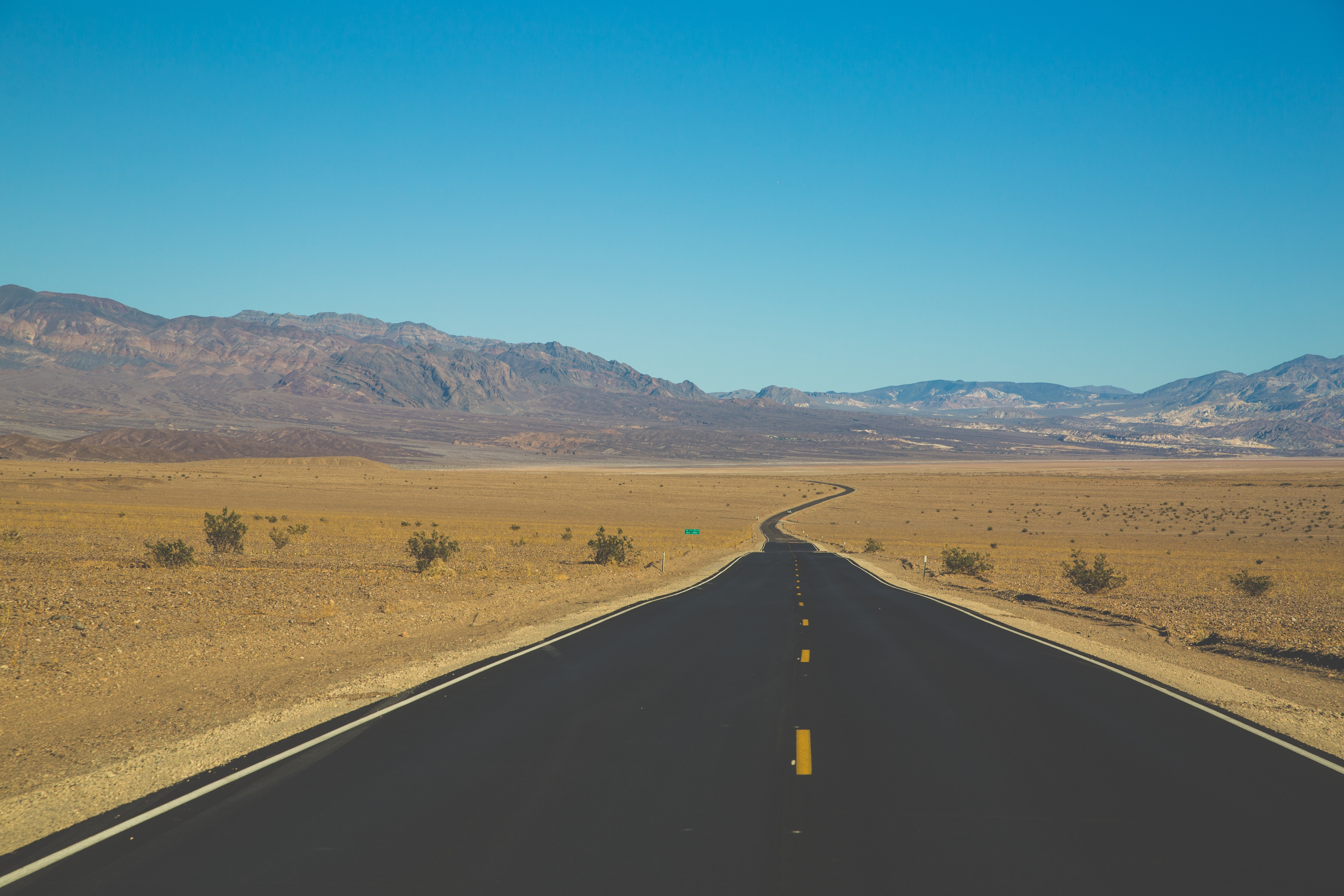 An empty road on arid flat terrain with rocky hills on the horizon