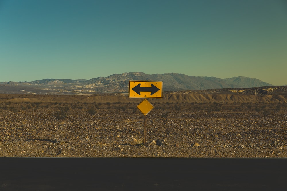 A yellow road sign with a black arrow pointing in both directions on the dry roadside near Death Valley