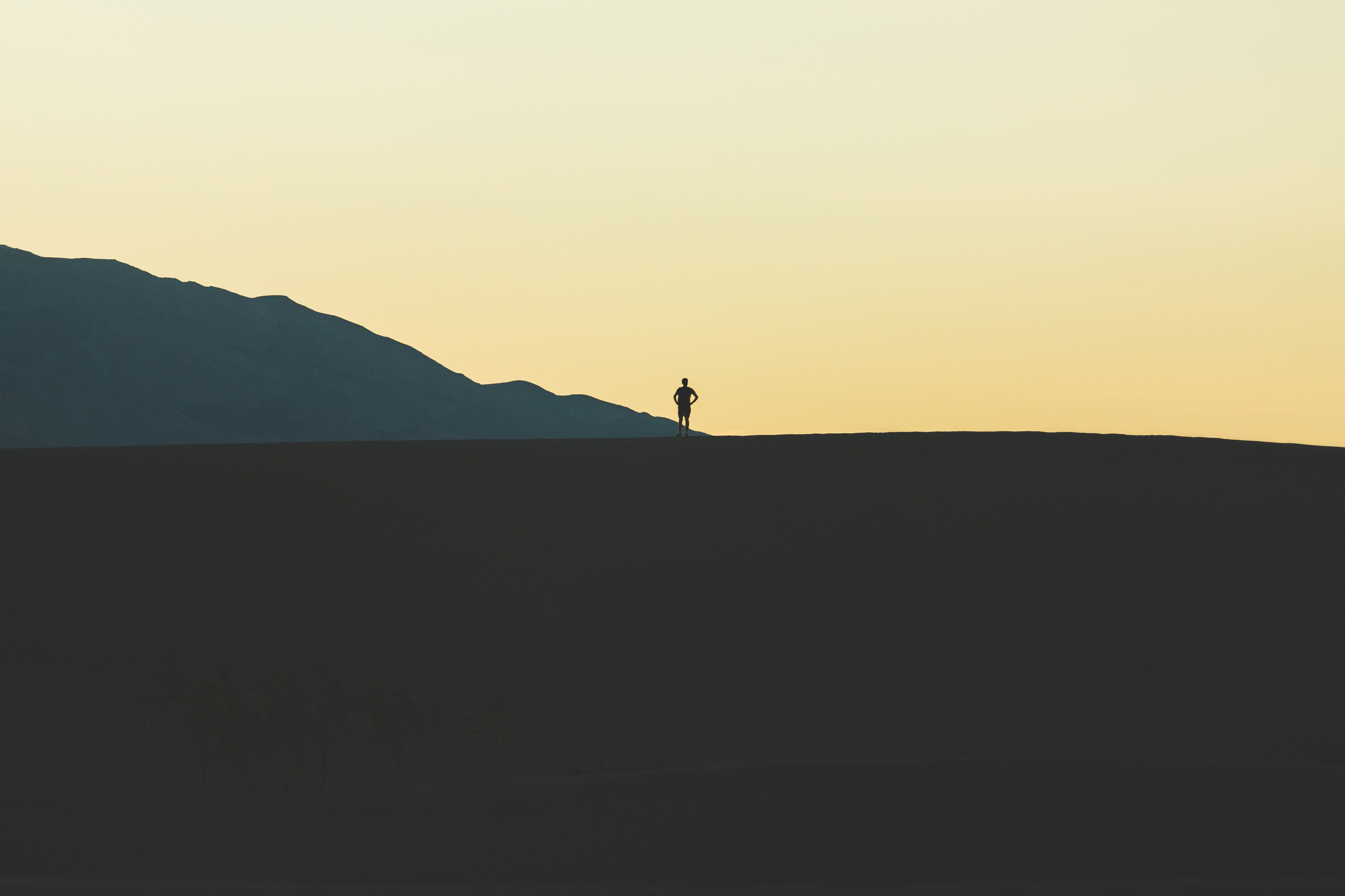 A person's silhoutte against the orange sky on a sand dune at Death Valley National Park