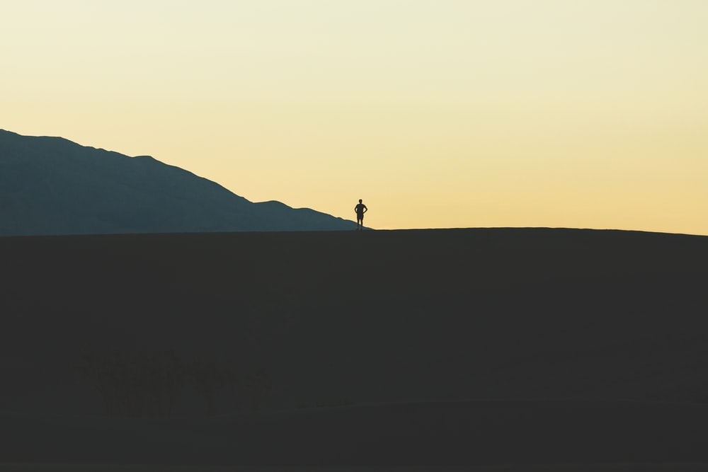 silhouette of person standing on mountain