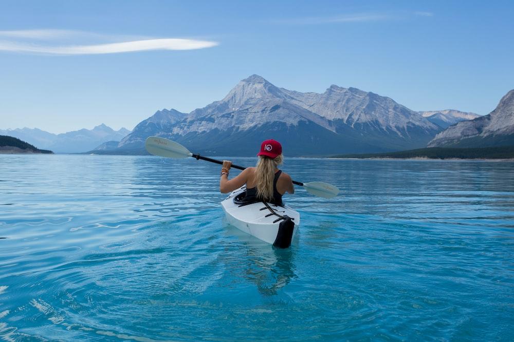woman wearing red hat riding on white kayak facing mountain alps