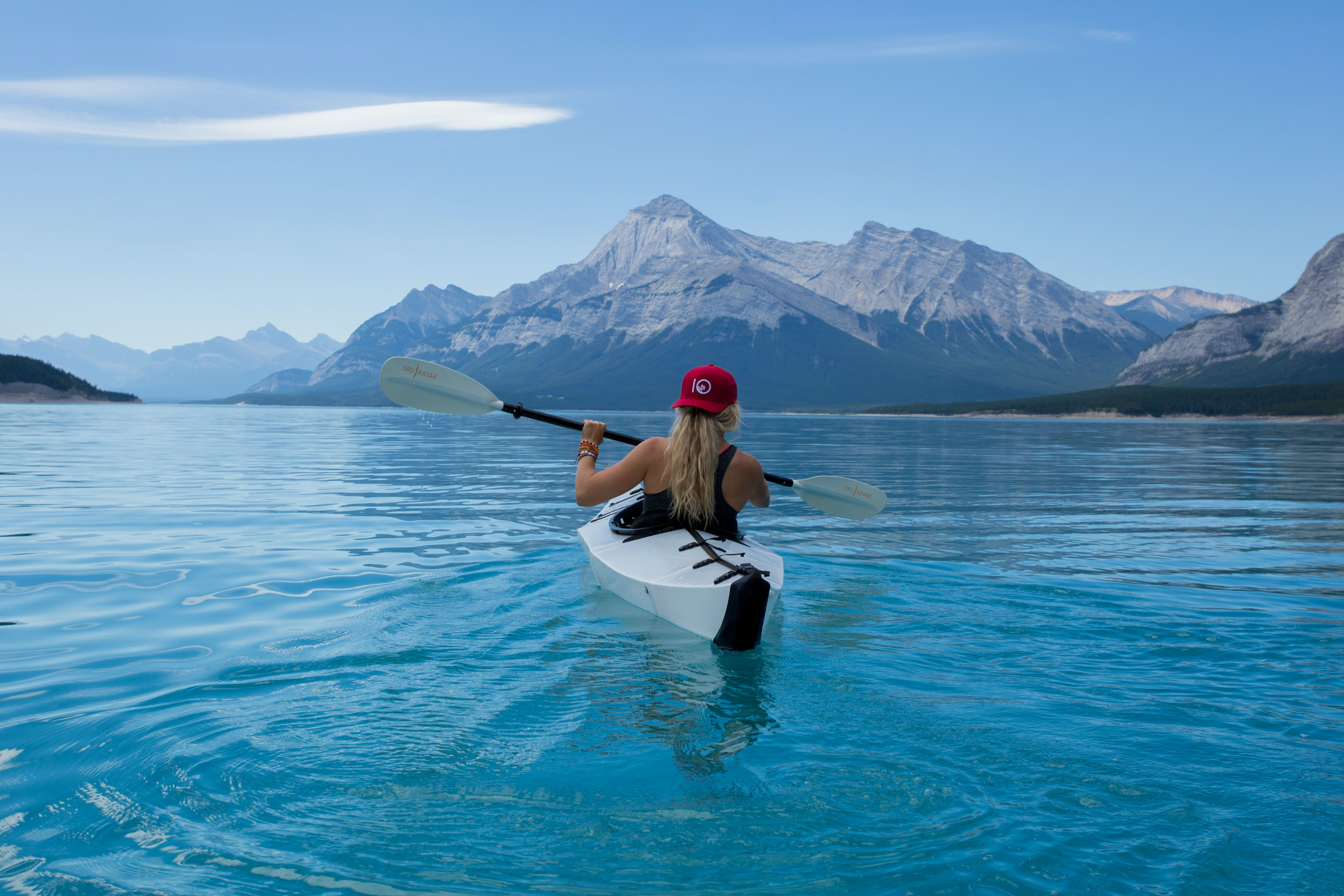 A woman wearing a red hat in a white kayak paddling on crystal blue water in Nordegg