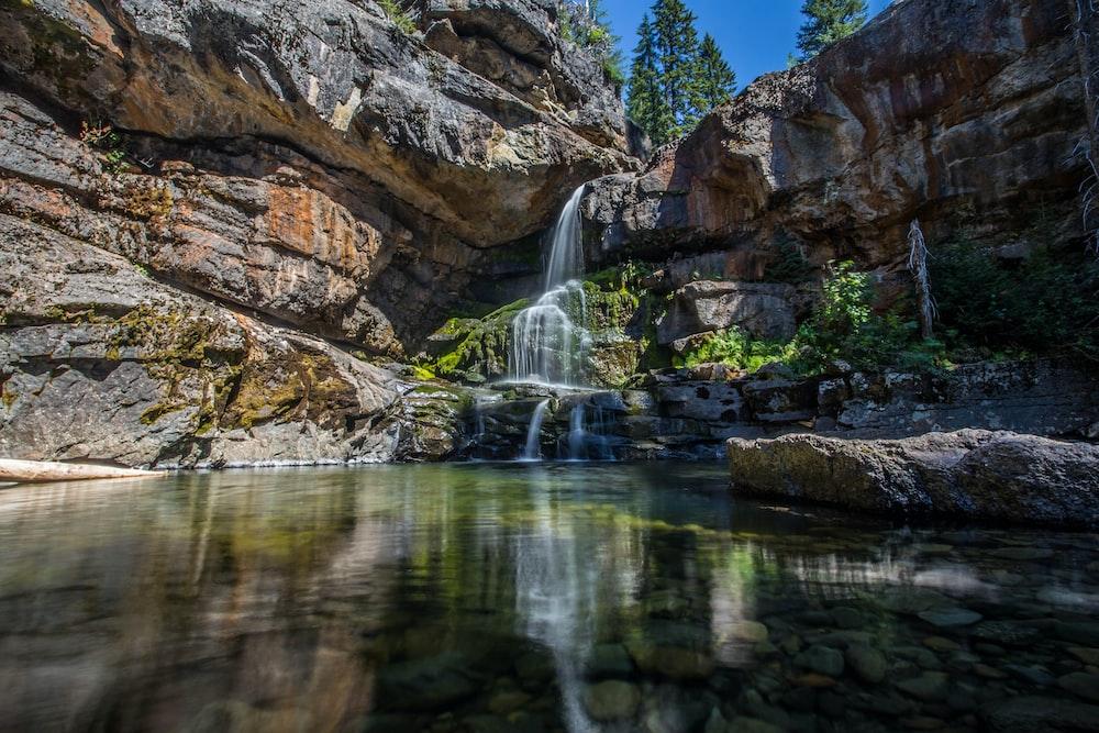 water falls in between brown rocks