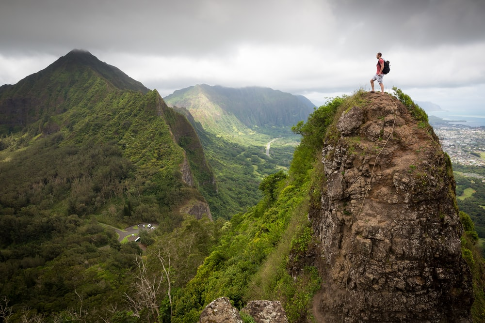 man on top of the mountain during daytime