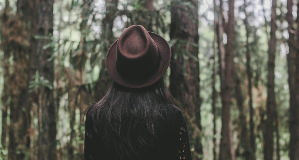 person wearing hat facing trees