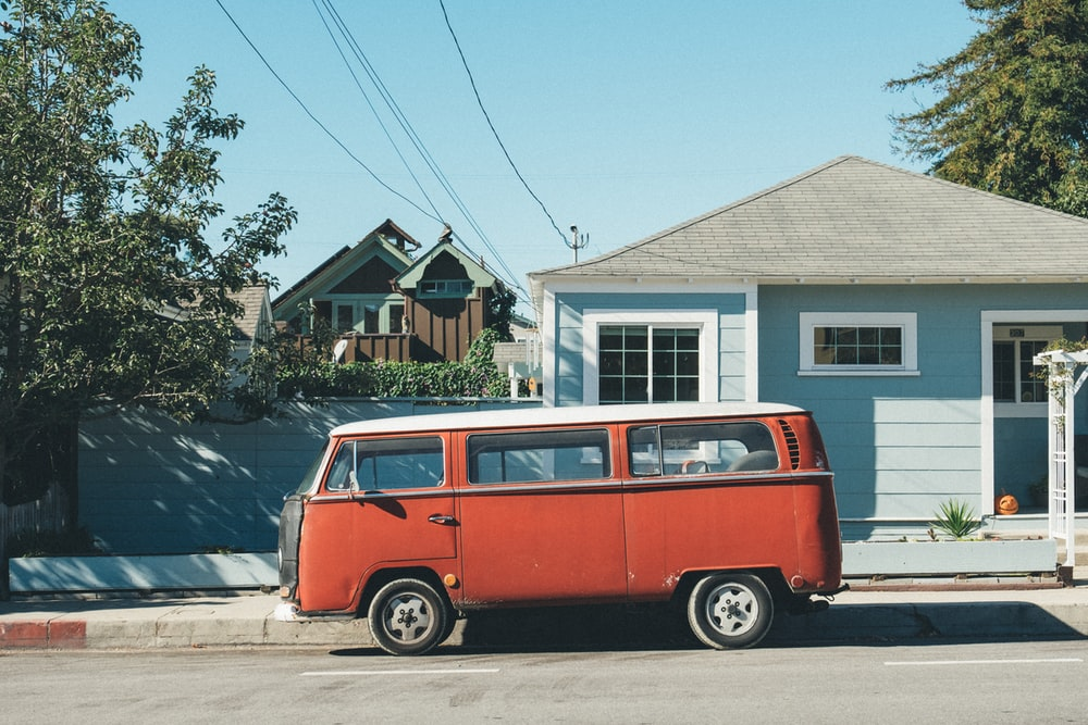 red Volkswagen Samba parked in front of teal house