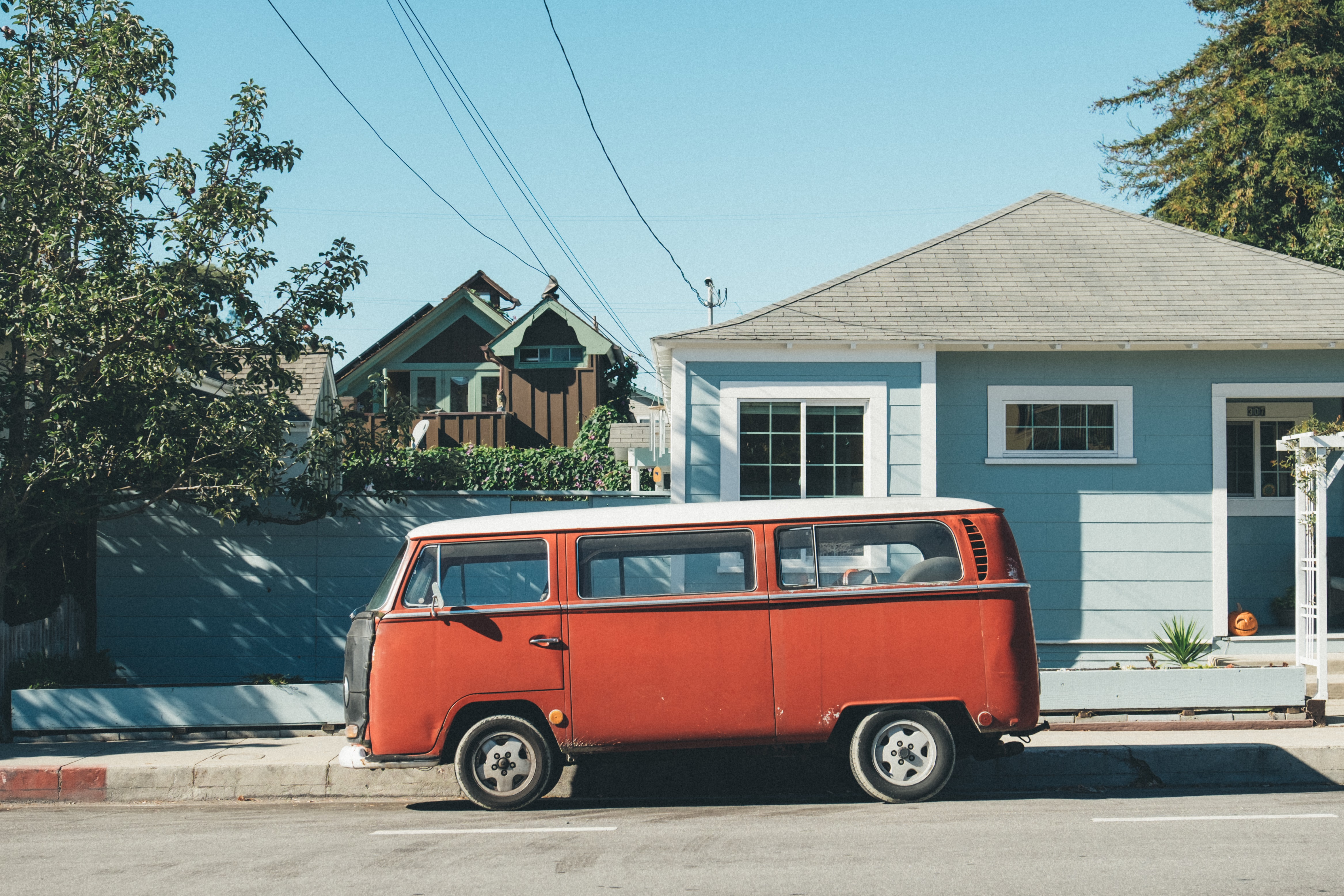 Vintage red Volkswagen van parked on the street in front of a light blue house