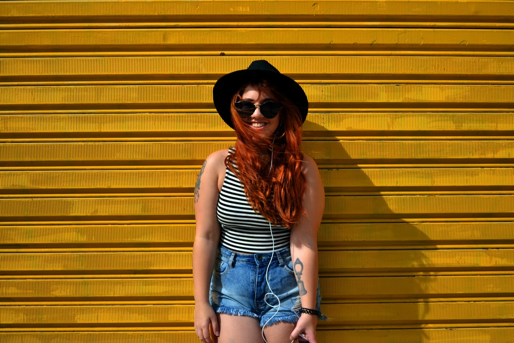A redhead woman standing in front of a yellow wall.