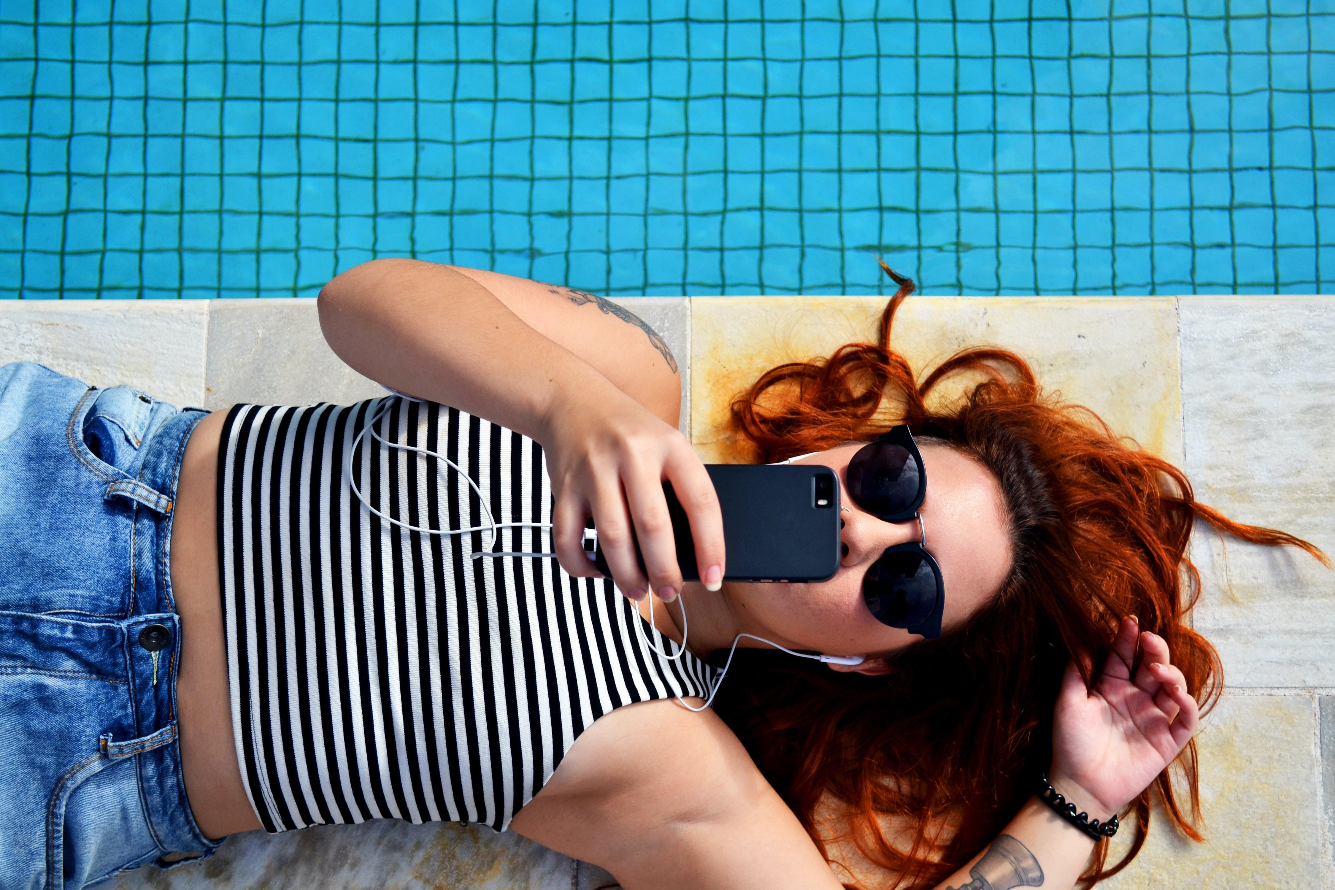 Sunglass wearing woman relaxing near swimmingpool with earphone plugged in iPhone at Sao Paulo