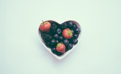 heart-shaped bowl with strawberries health teams background