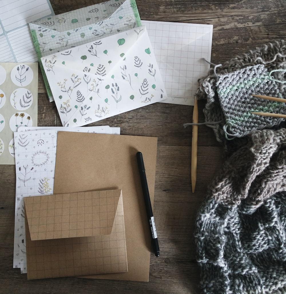 black pen beside envelop and knit scarf