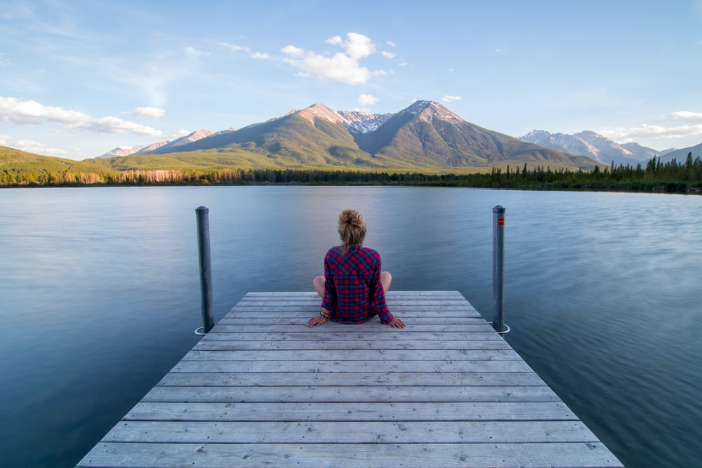 woman sitting on dock bridge near lake during daytime