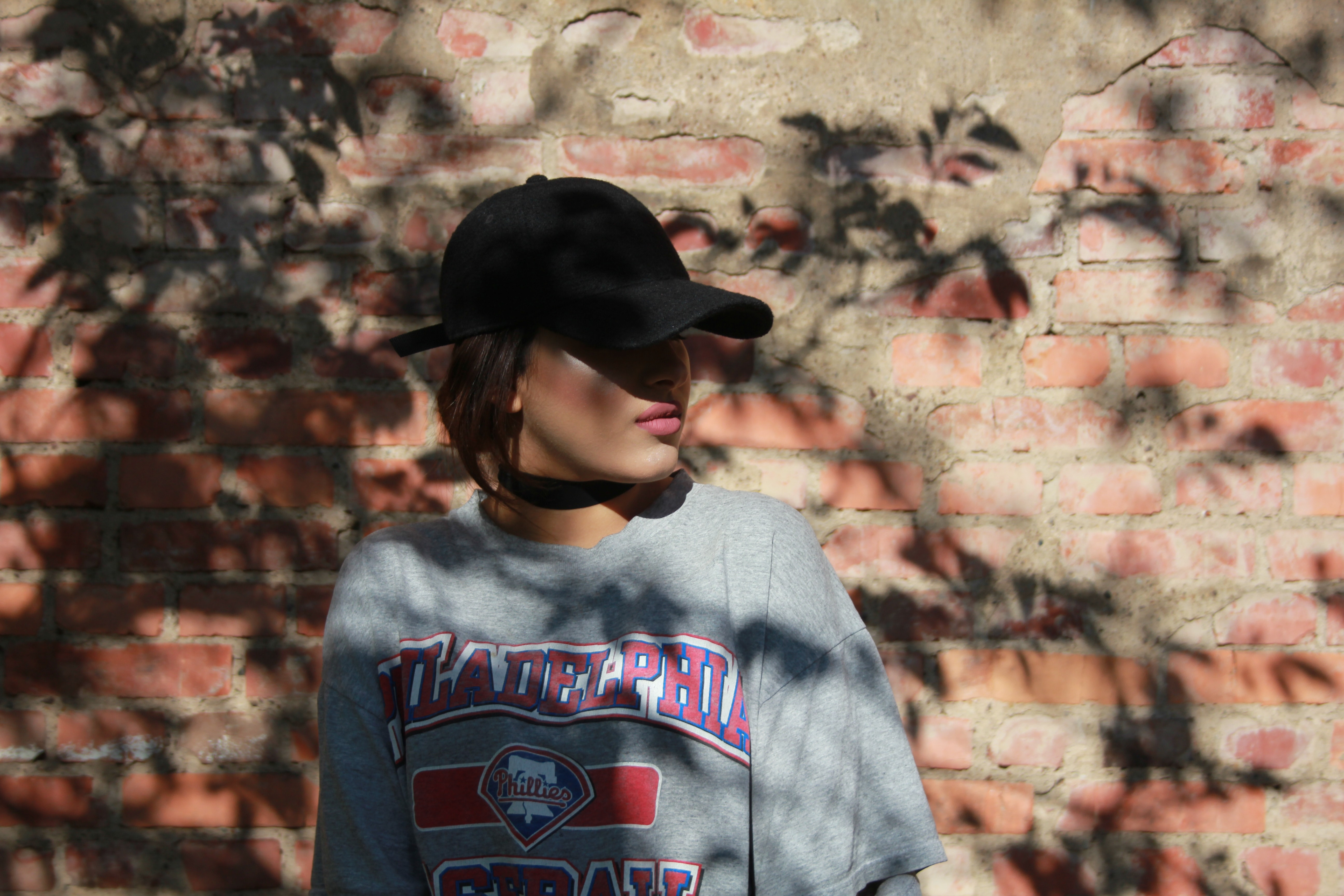 A lady wearing lipstick, cap and a t-shirt with logo on it standing by a brick wall