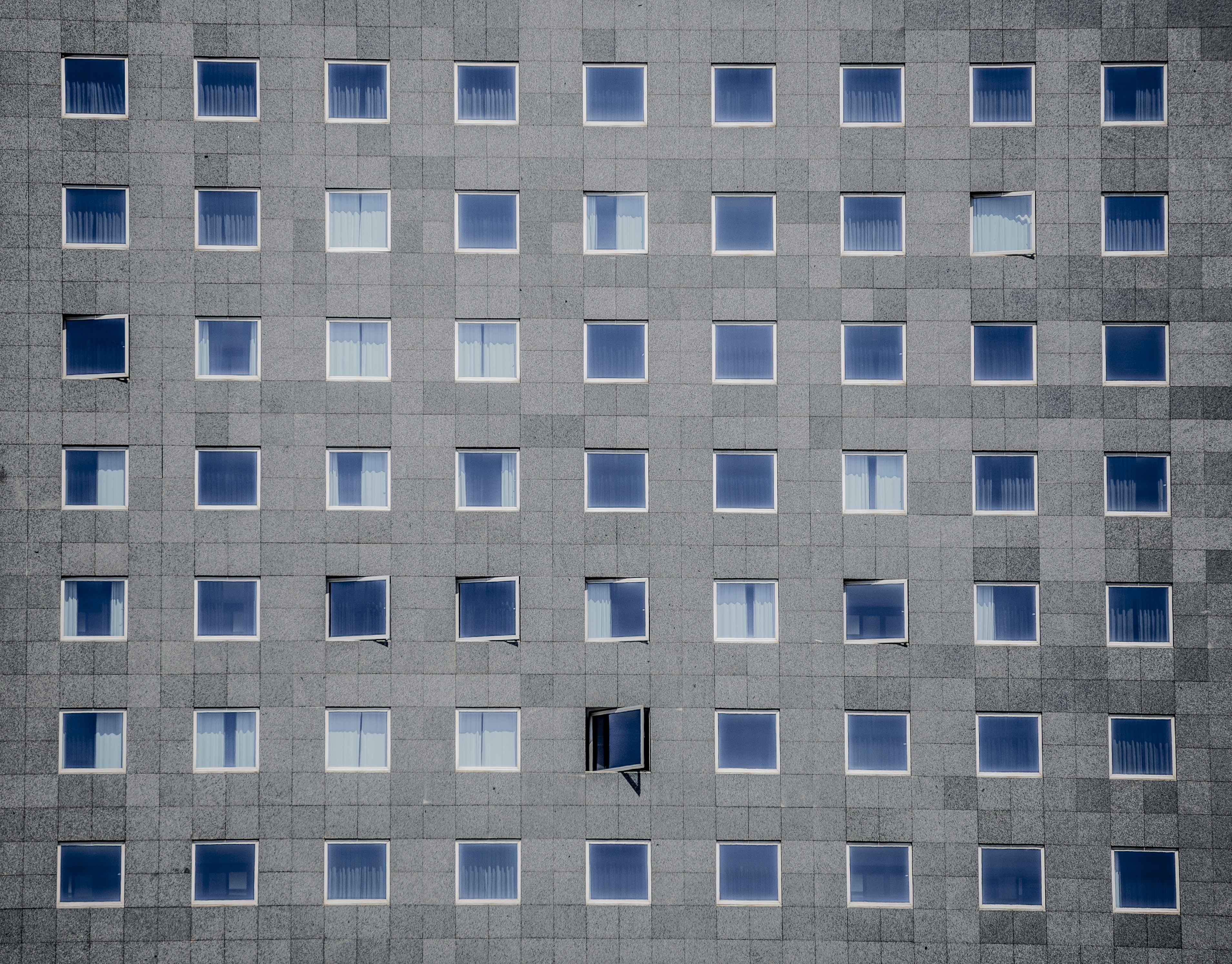 A regular arrangement of square windows in a gray tiled facade
