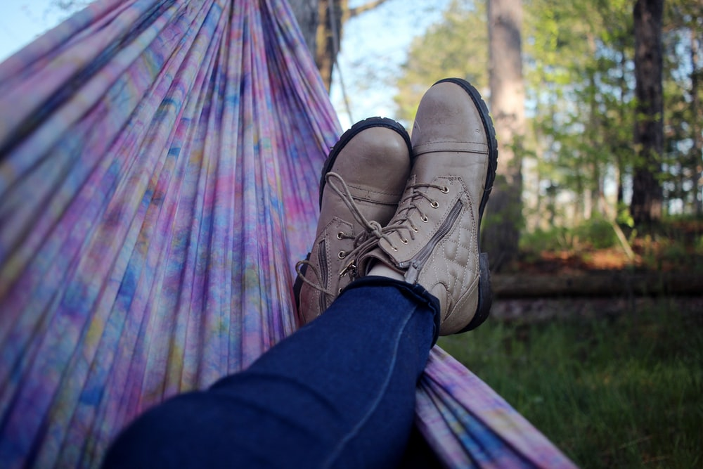 person lying on pink and purple hammock surrounded with trees