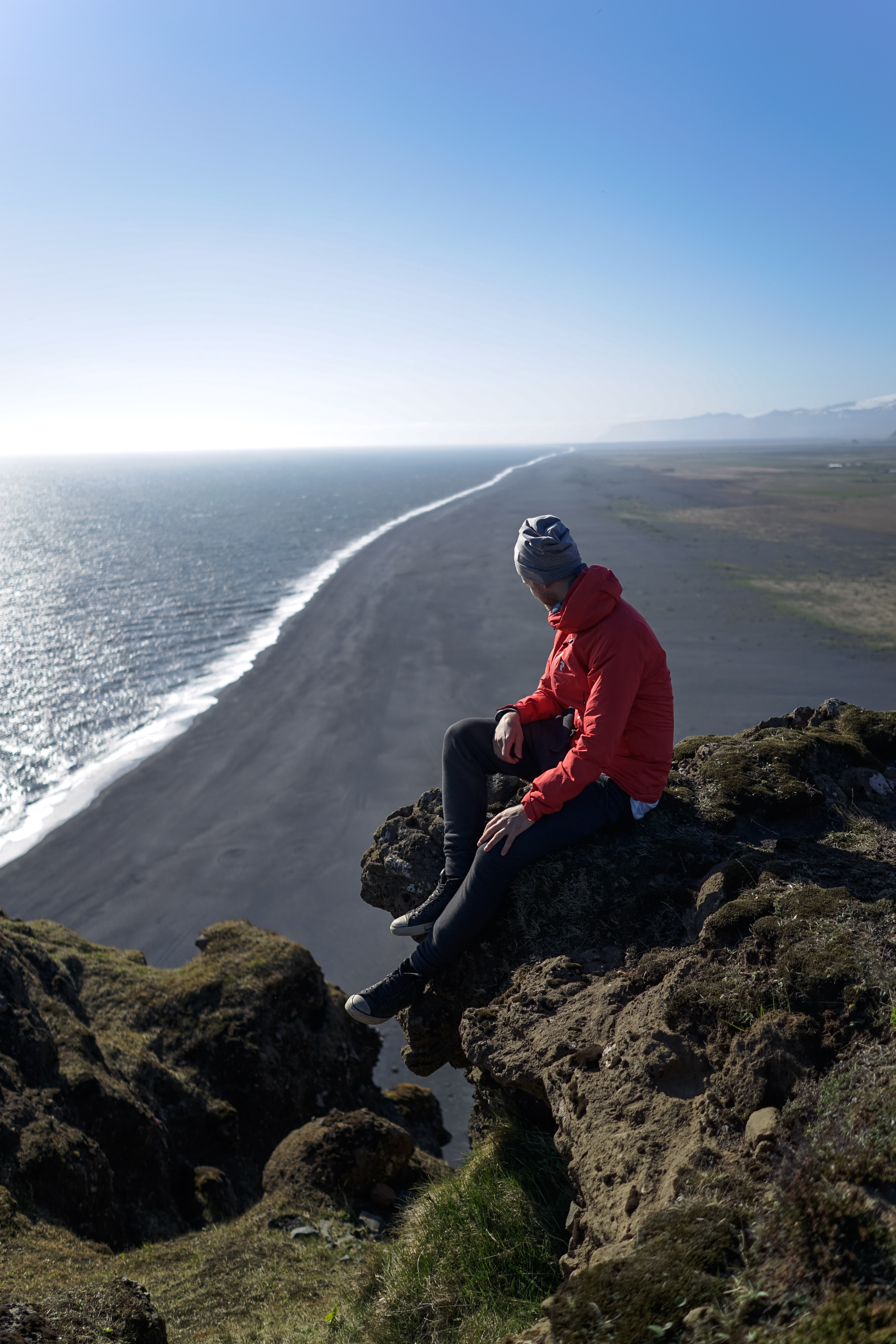 A man looks out over the beach and sea in Dyrhólaey