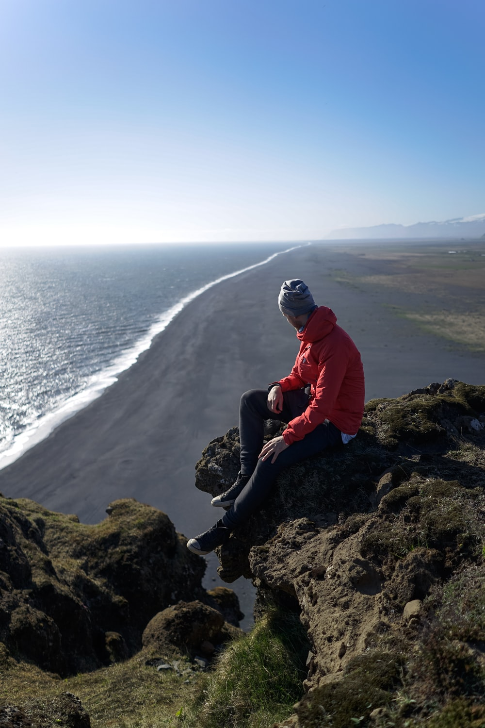 man sitting on mountain cliff near body of water