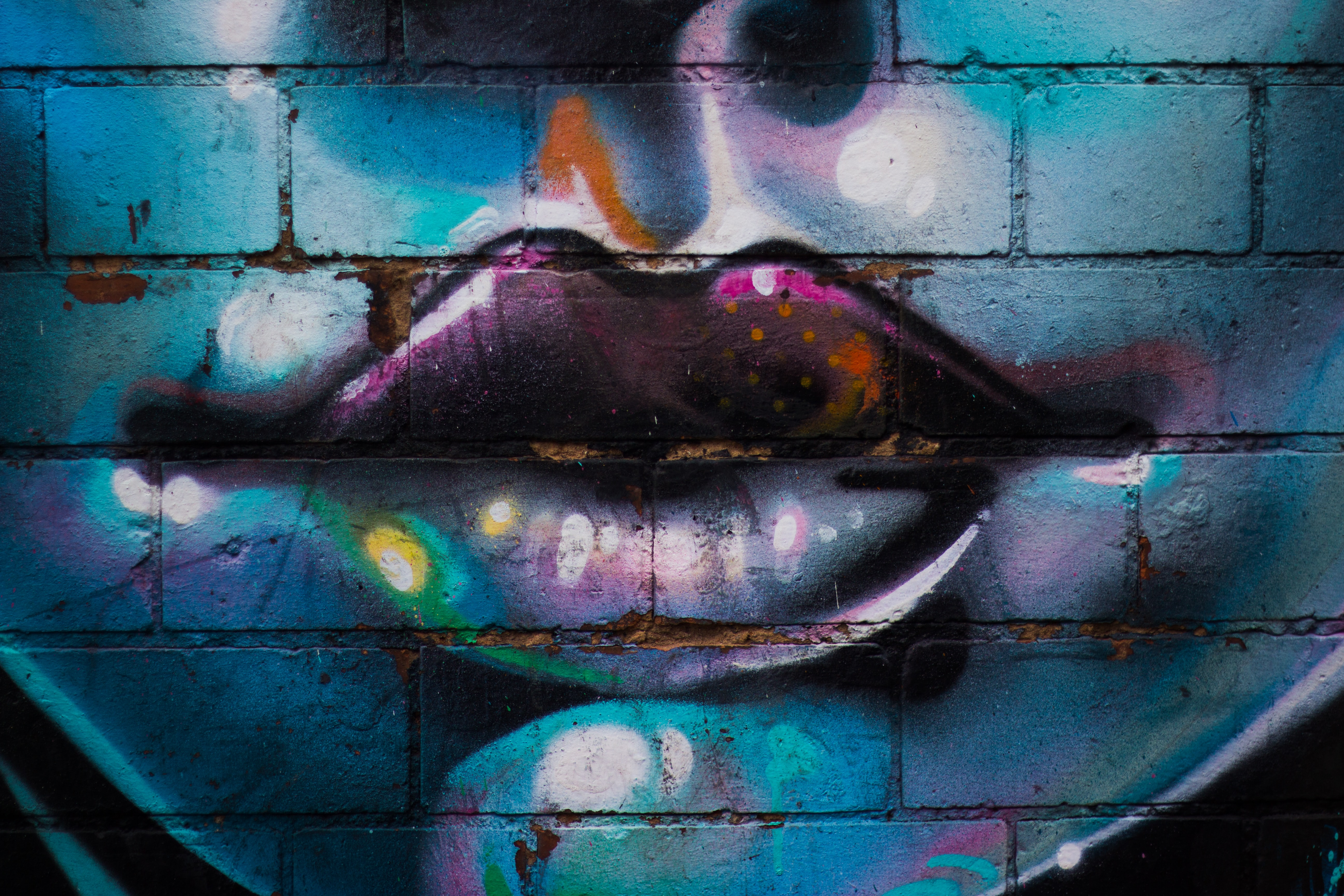 Colorful lips, chin and nose of a face painted on a brick wall.