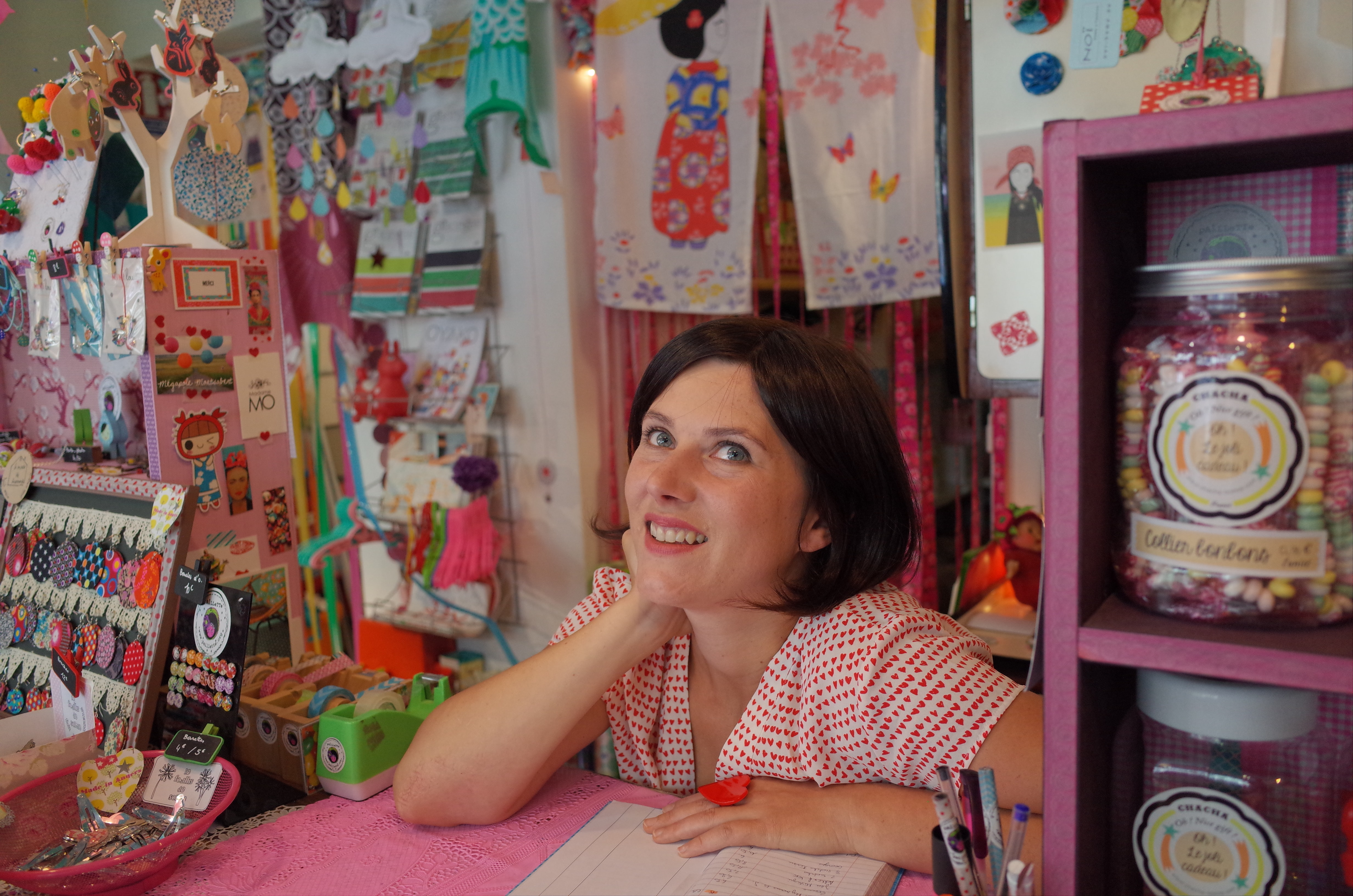 A smiling woman behind a counter with colorful trinkets around her