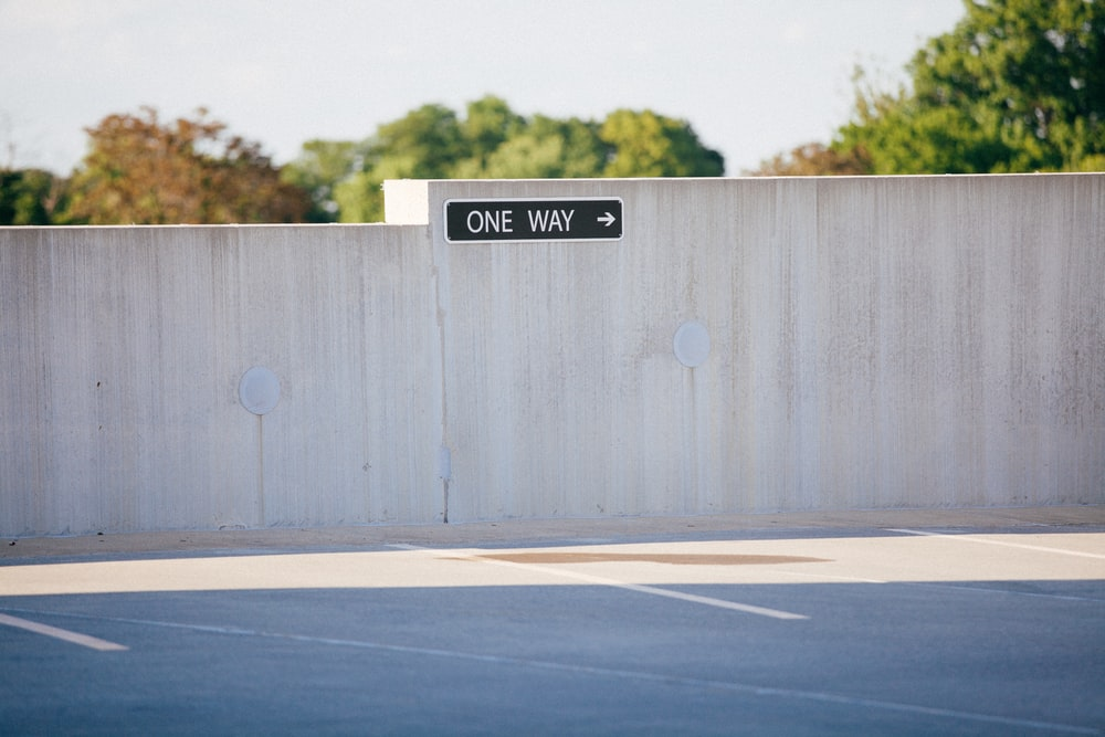 black and white one way signage on gray concrete wall