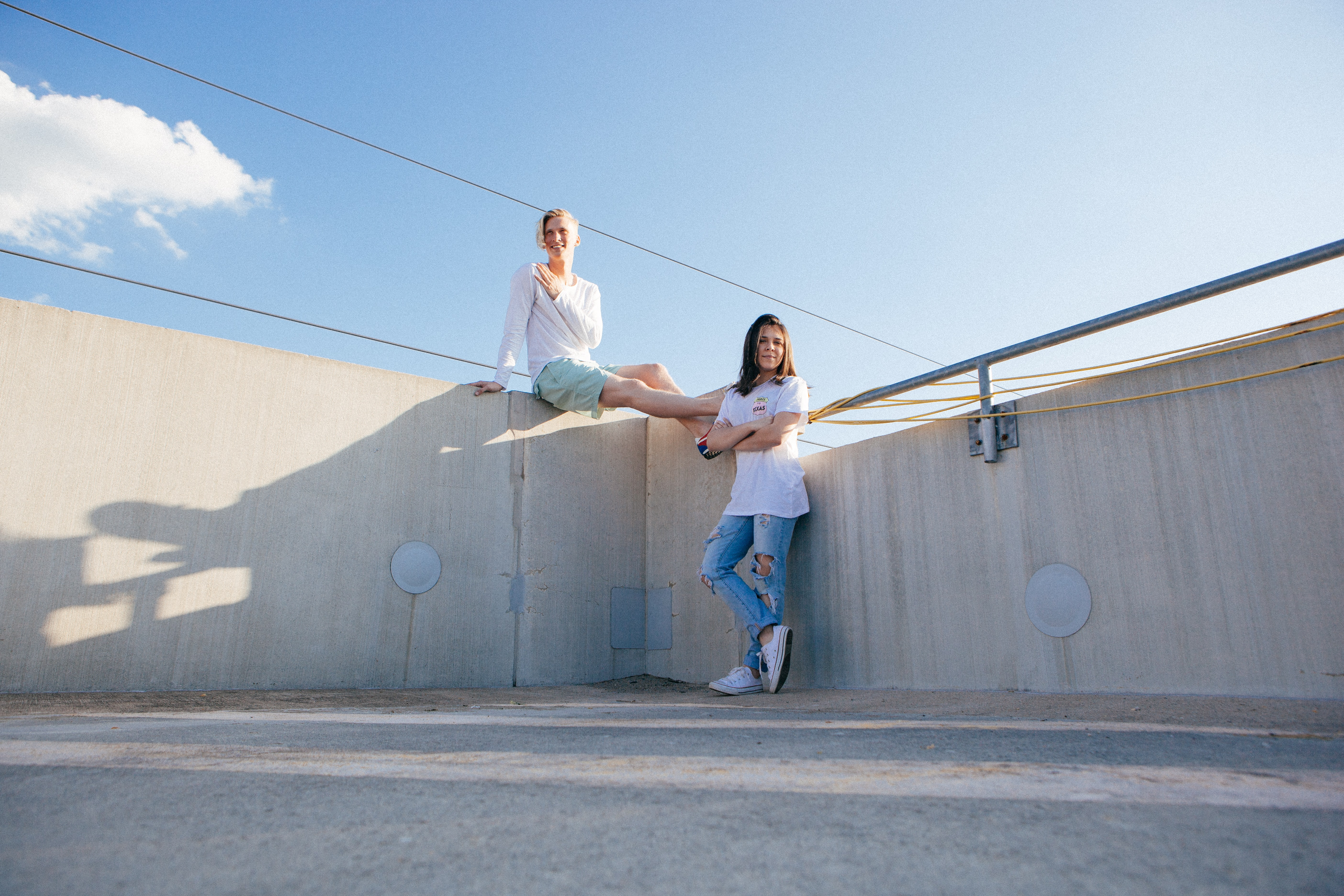 Two young women in white t-shirts pose in a concrete structure beneath a blue sky