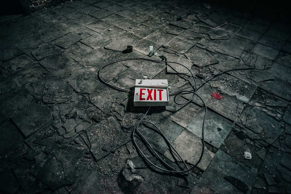 grey exit sign board on grey pavement