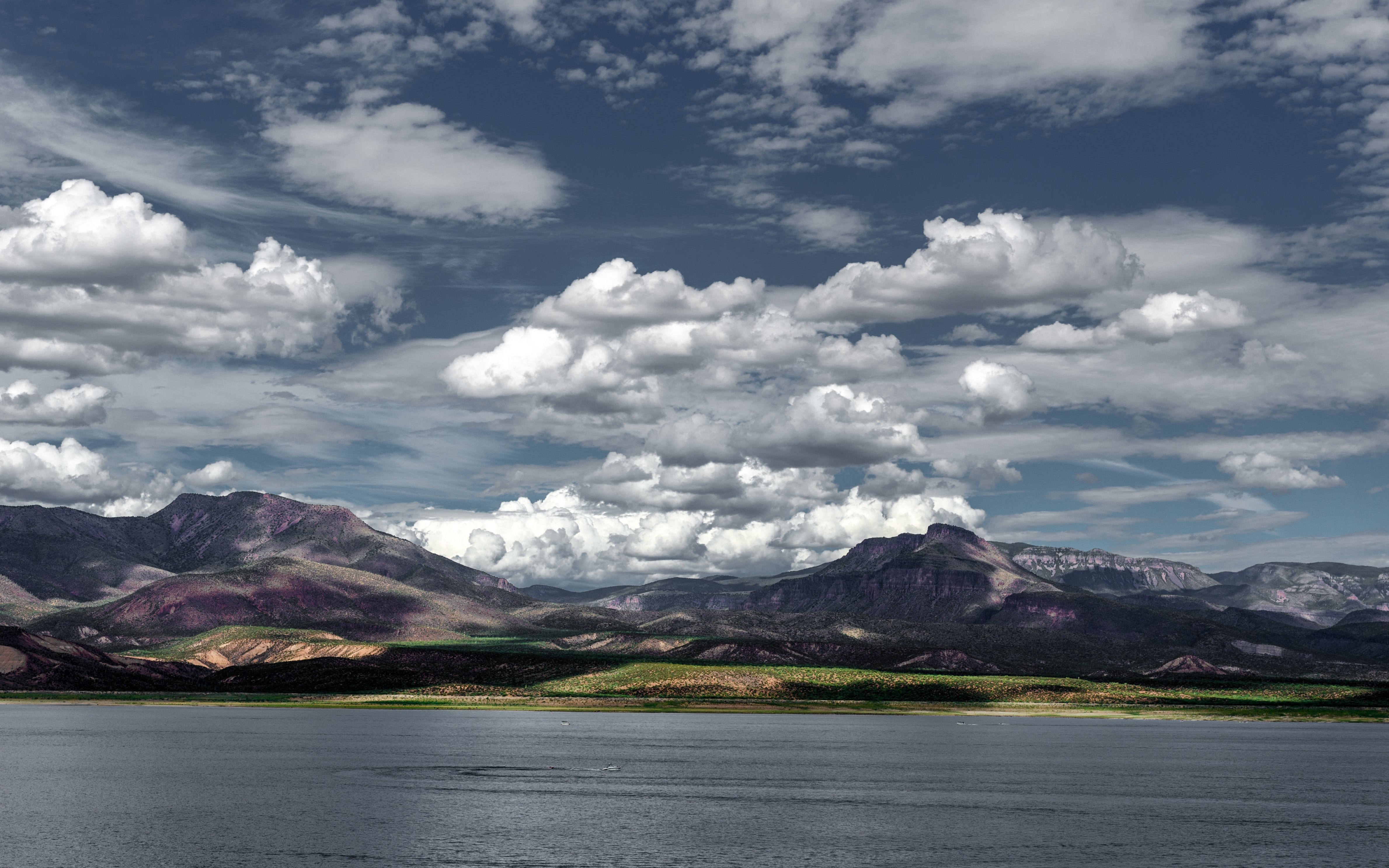 Beautiful mountain view with white fluffy clouds over a lake Roosevelt