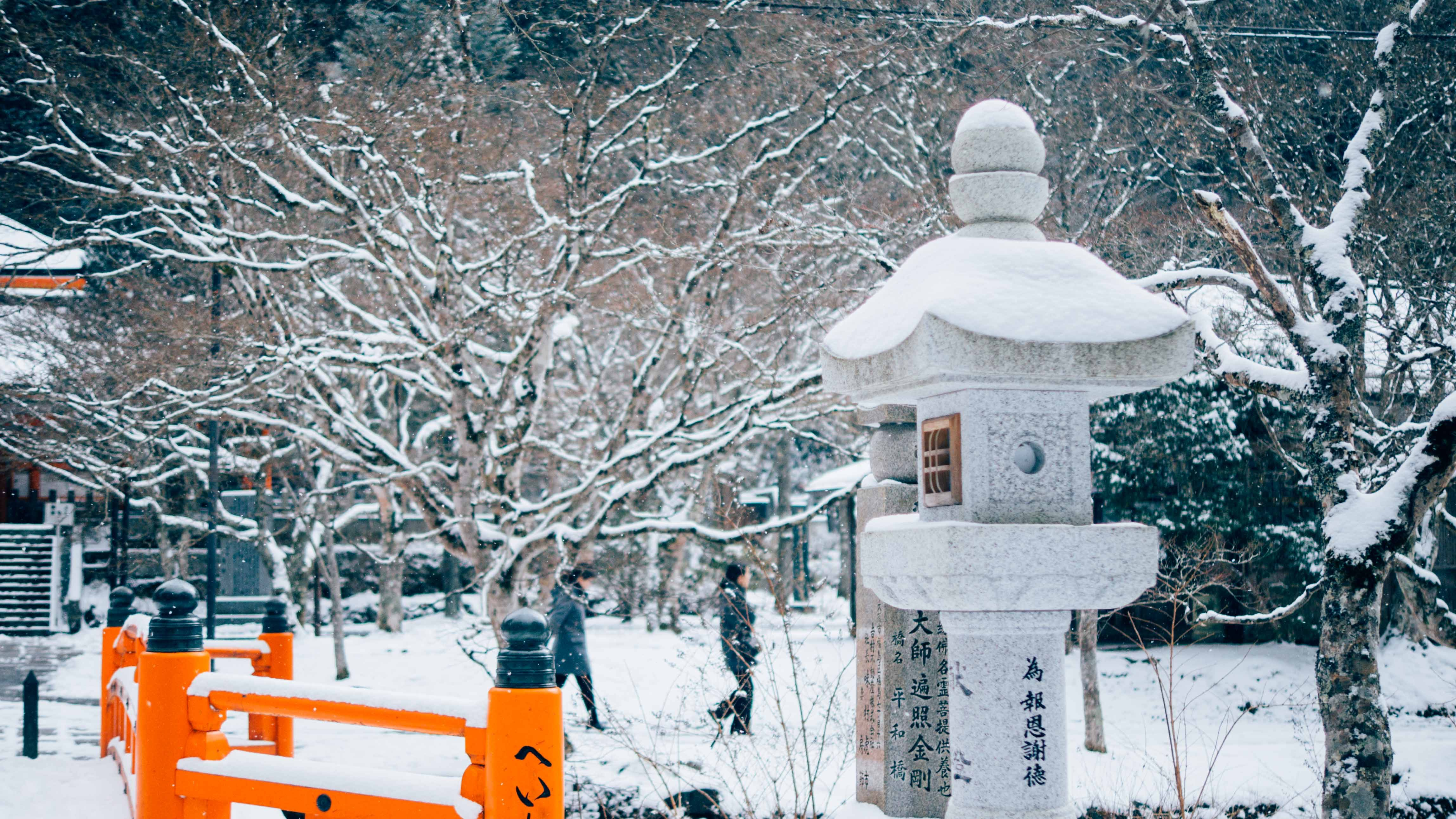 Two people walk in snow-covered landscape at Koyasan
