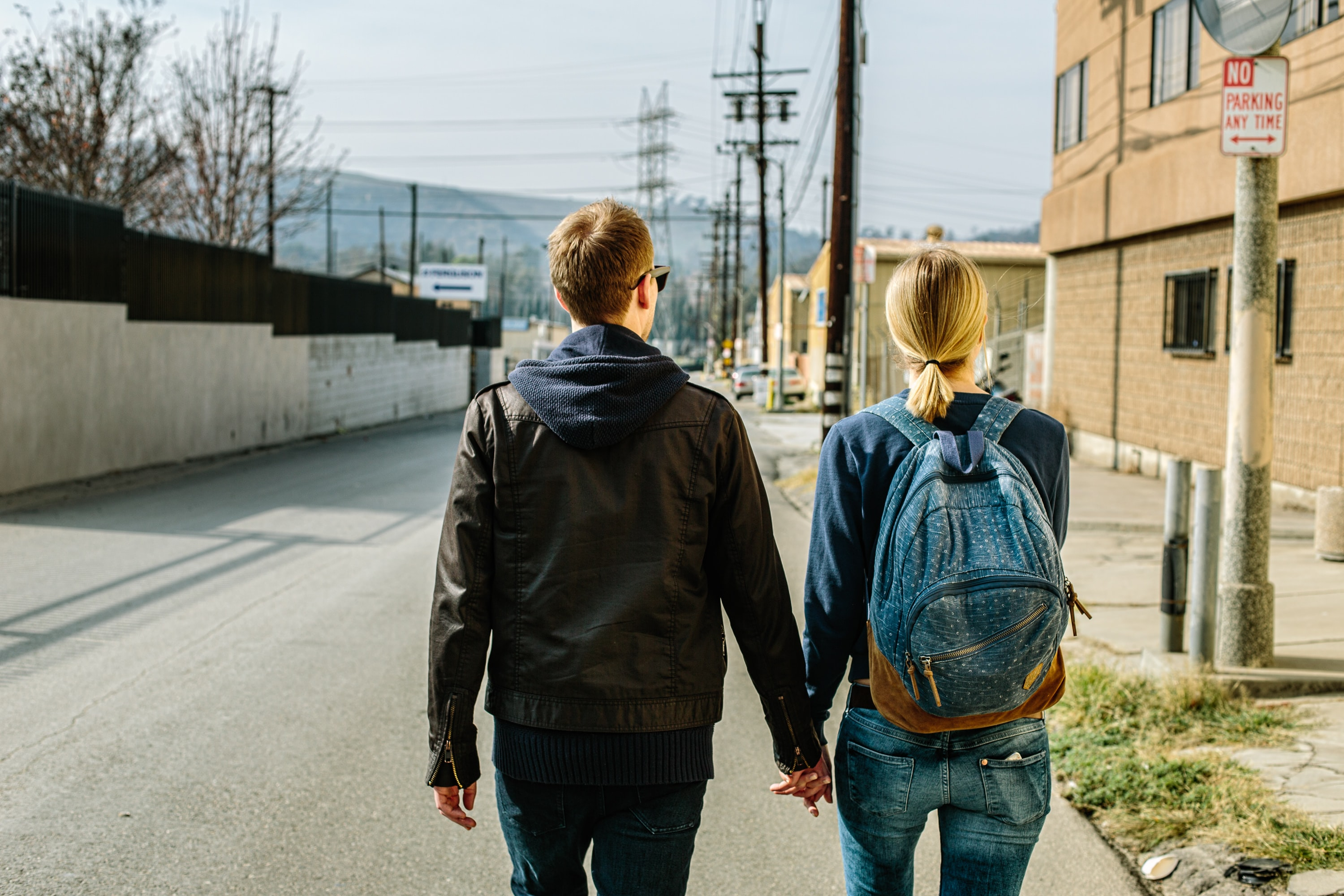 A man and woman wearing a backpack walk along a city street holding hands