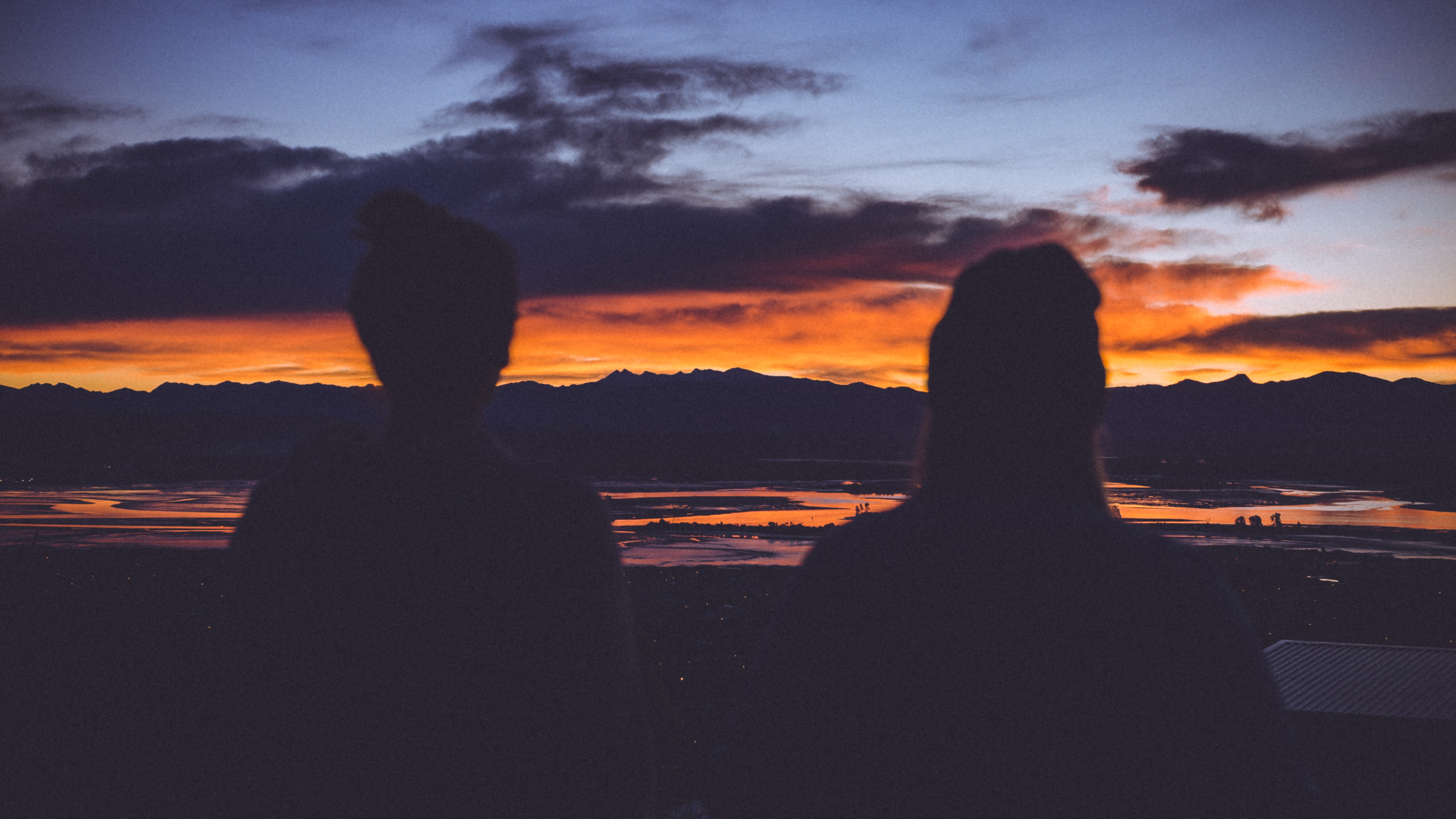 silhouette photo of two women starring at sunset
