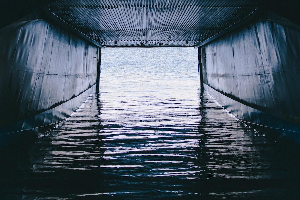 grayscale photo of a bridge over the sea
