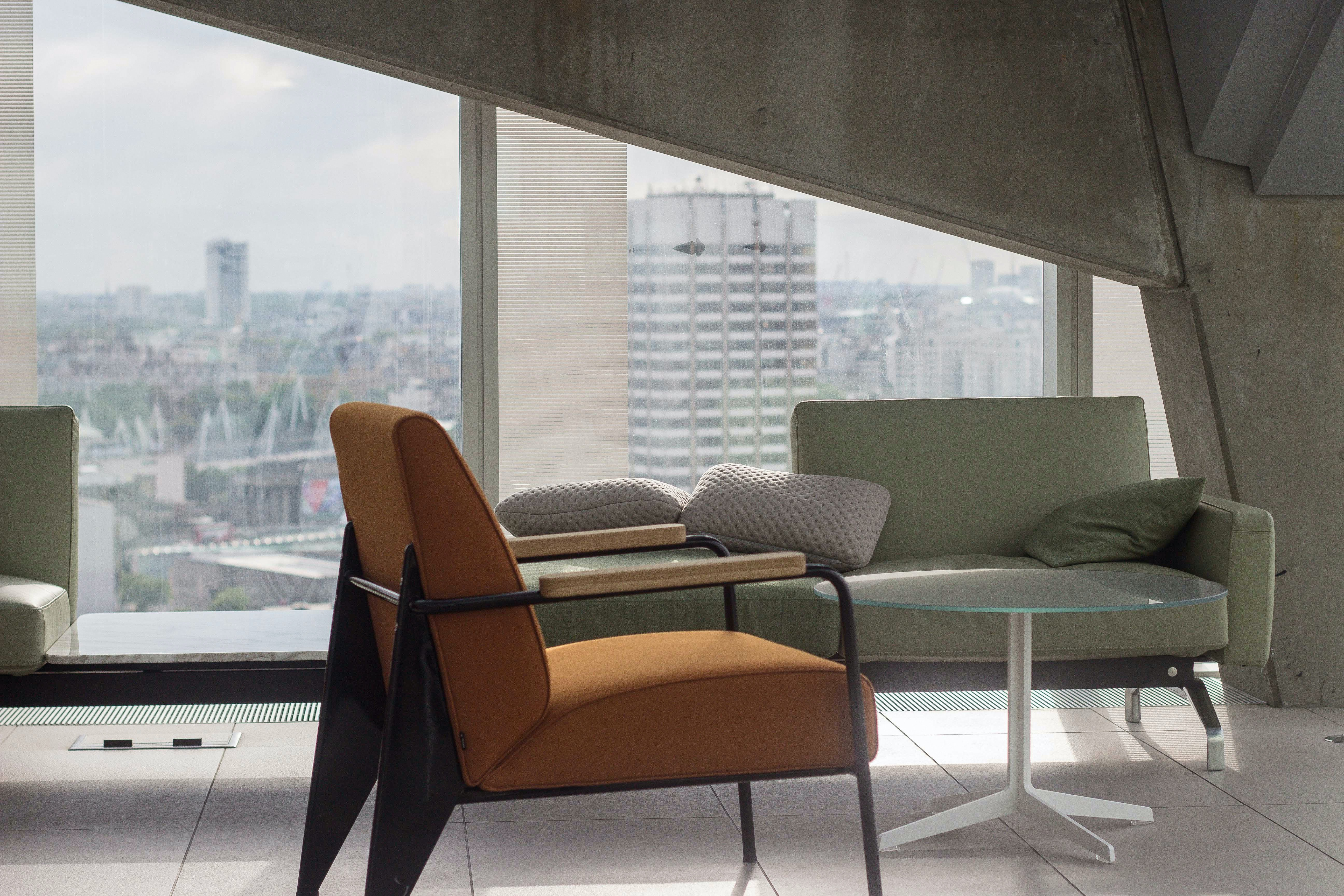 A chair, a coffee table and a sofa next to a floor-to-ceiling window and a bare wall