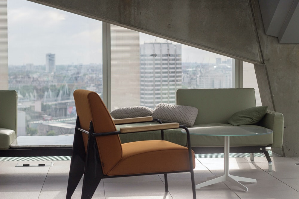 orange fabric padded armchair with black metal base near round clear glass-top table and gray sofa