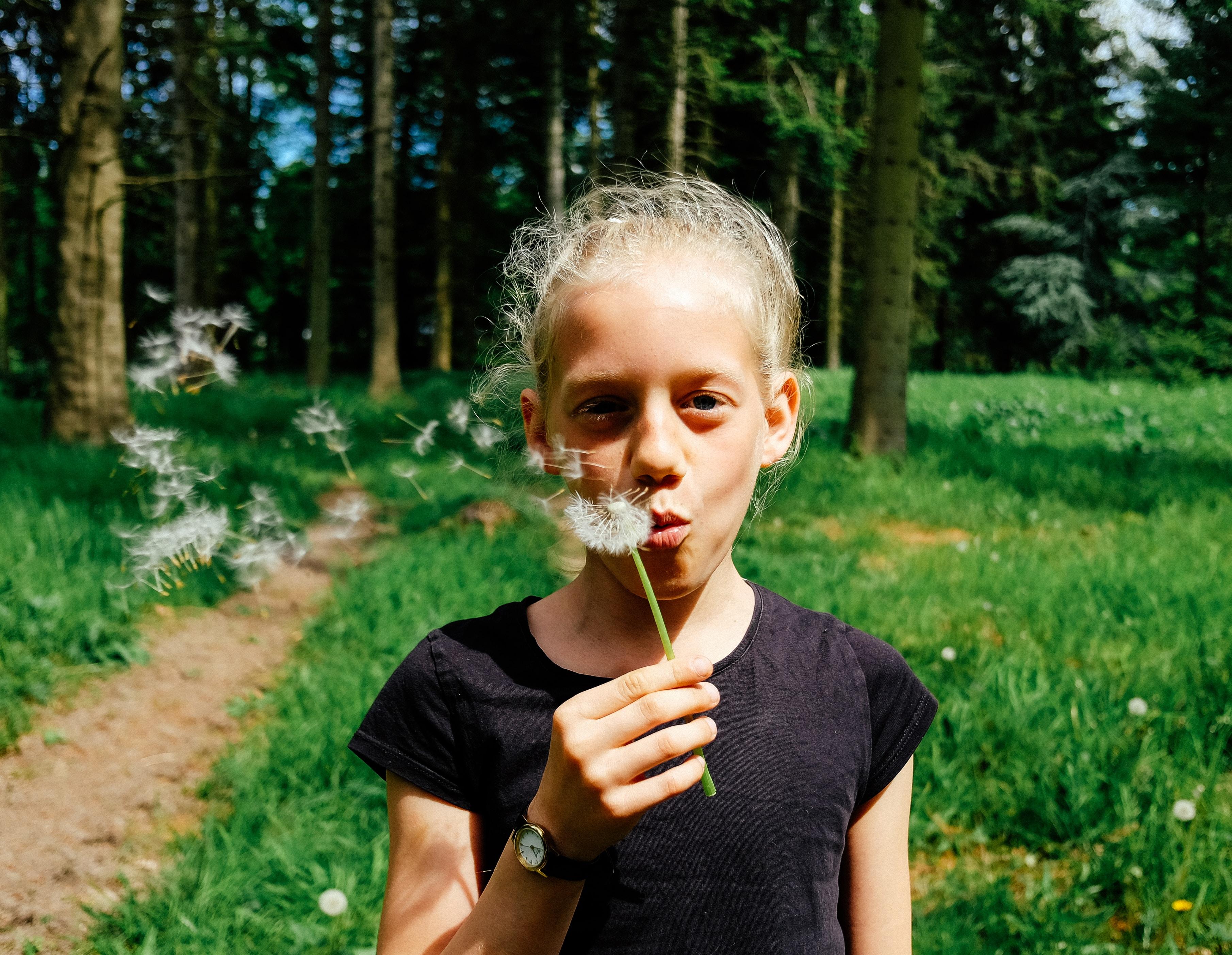 woman in black shirt blowing dandelion