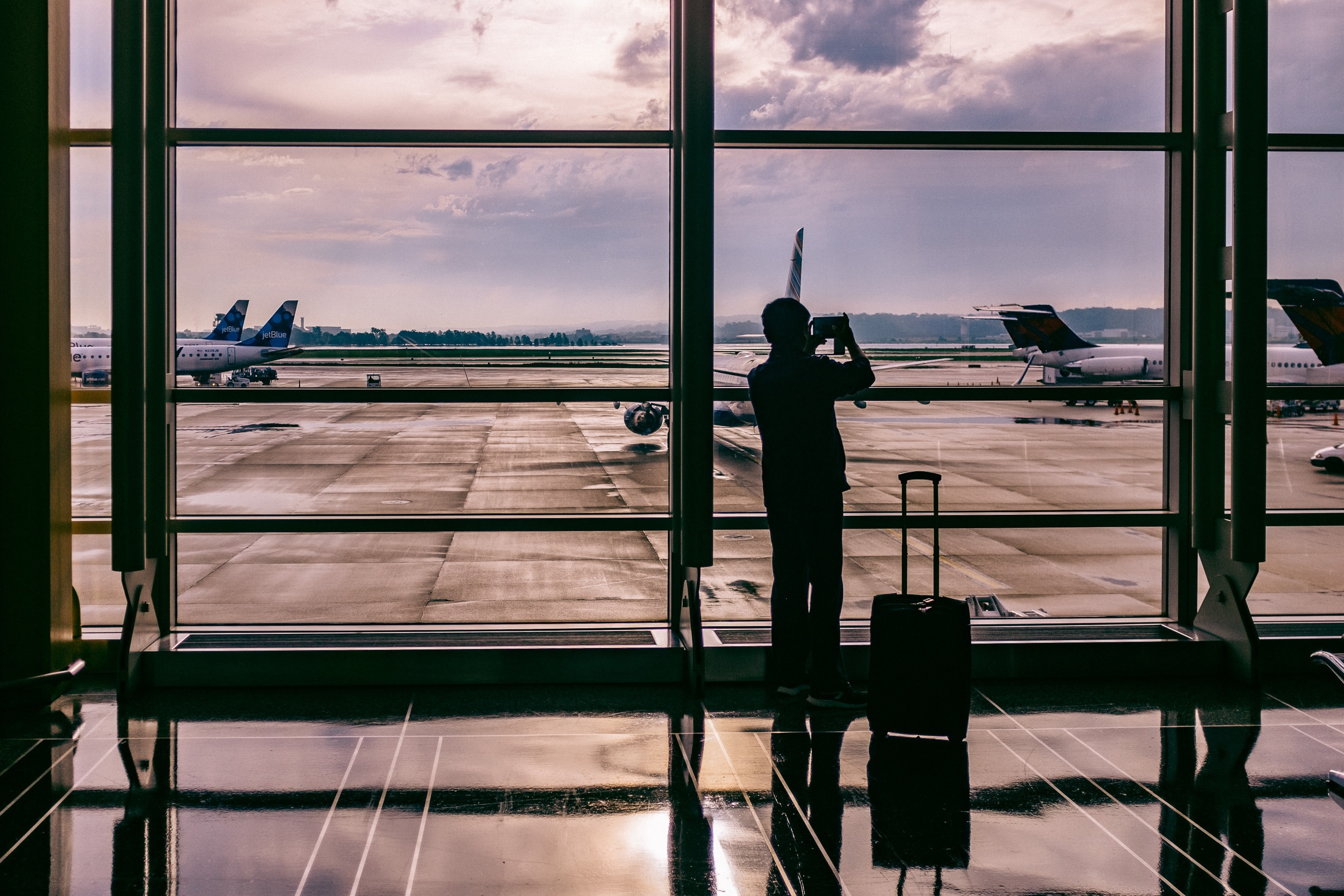 A silhouette of a man taking photos at the floor-to-ceiling window in an airport